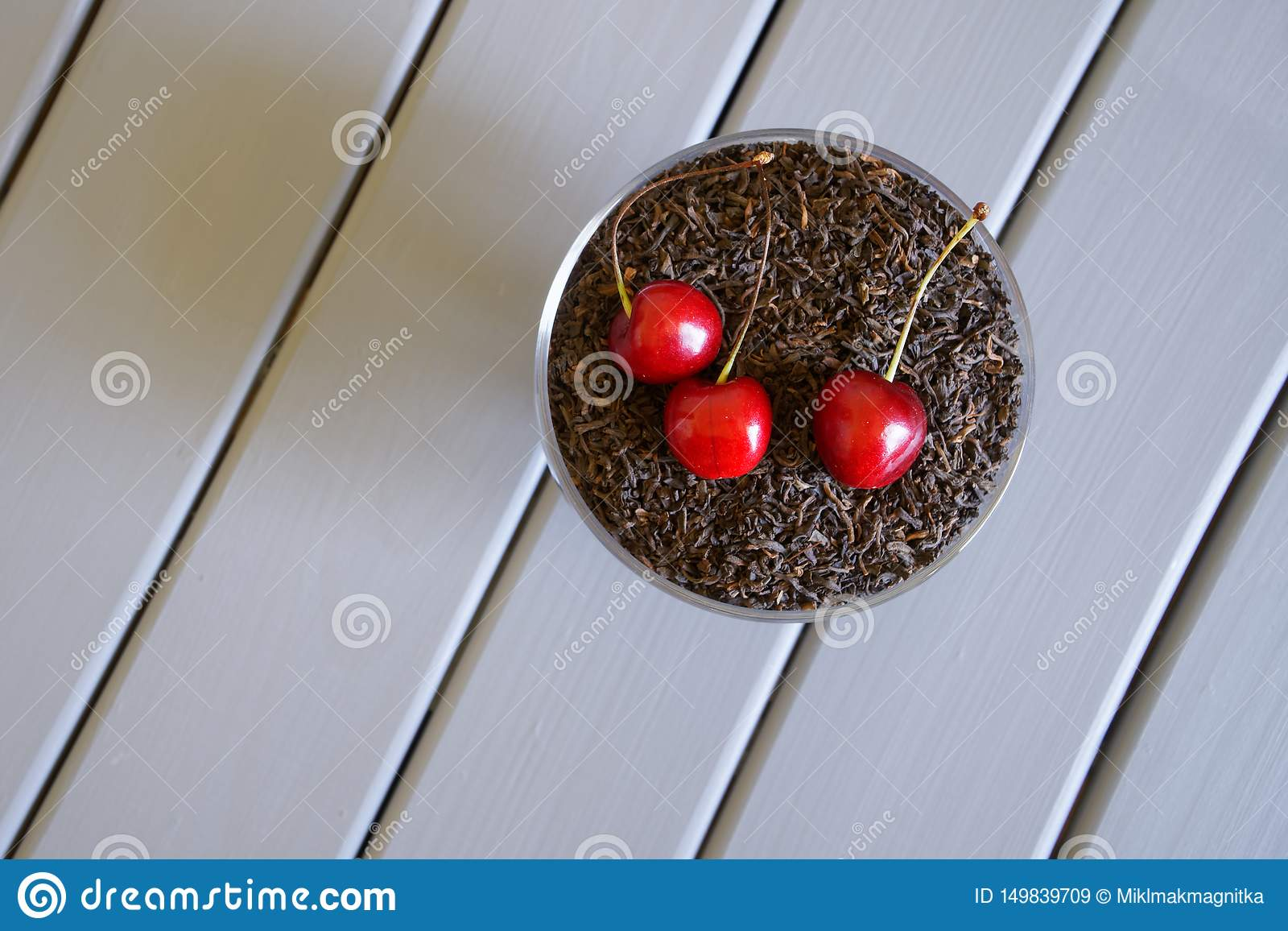 Traditional black tea with red cherries on a light background. Fruit flavor favorite drink