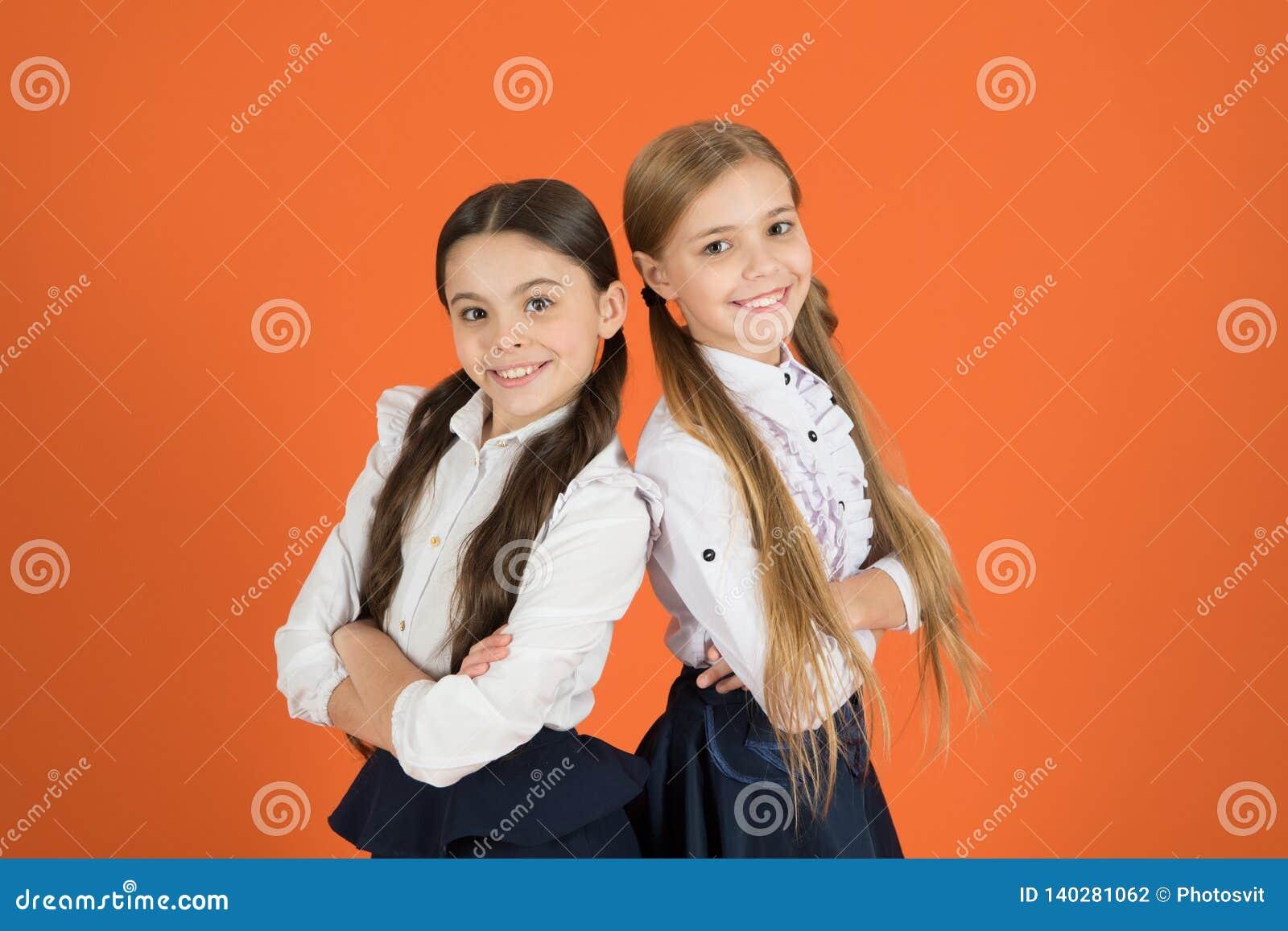 92cb9e98f4cd School children with a fashion forward look. Cute schoolgirls. Small girls  in pigtails dressed for school. Back to school fashion.
