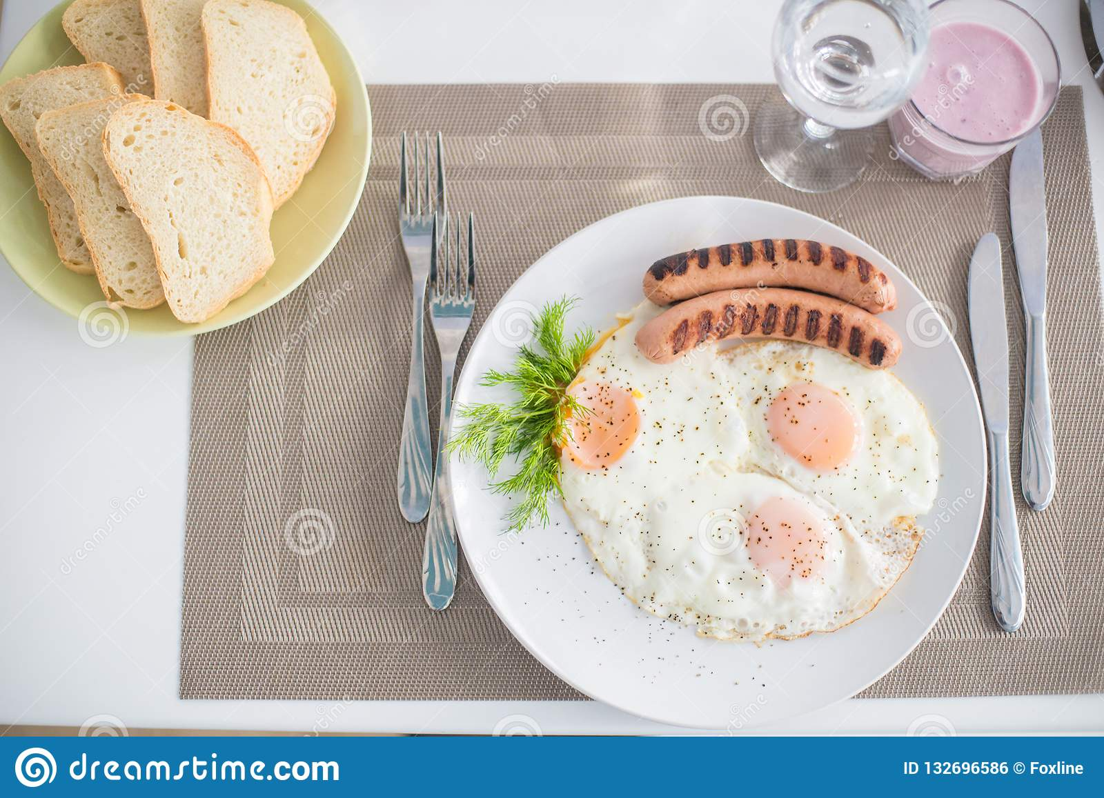 Traditional breakfast with sausages, fried eggs with ground black pepper and bread