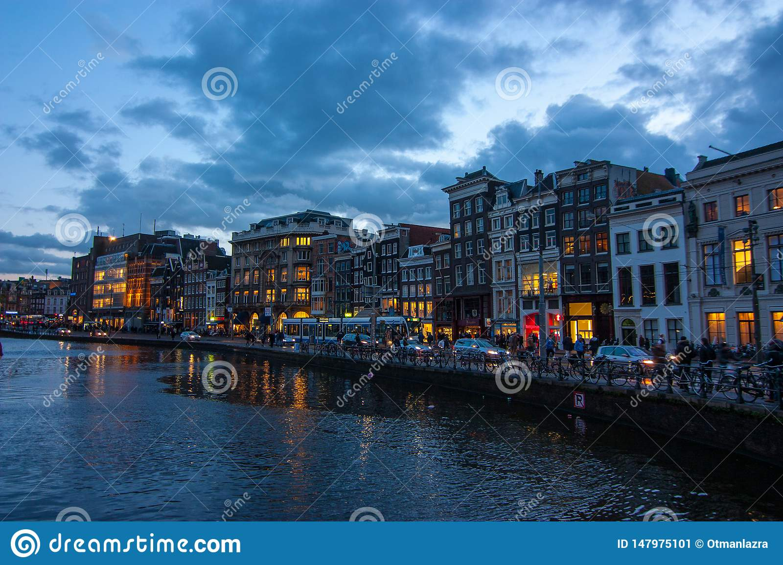 Traditional canal houses on the Damrak at dusk in Amsterdam.