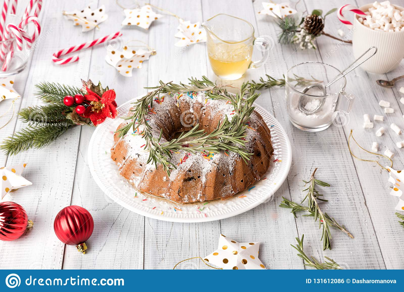 Traditional Christmas fruit cake on a white wooden table. Homemade pudding with festive decorations, candy canes