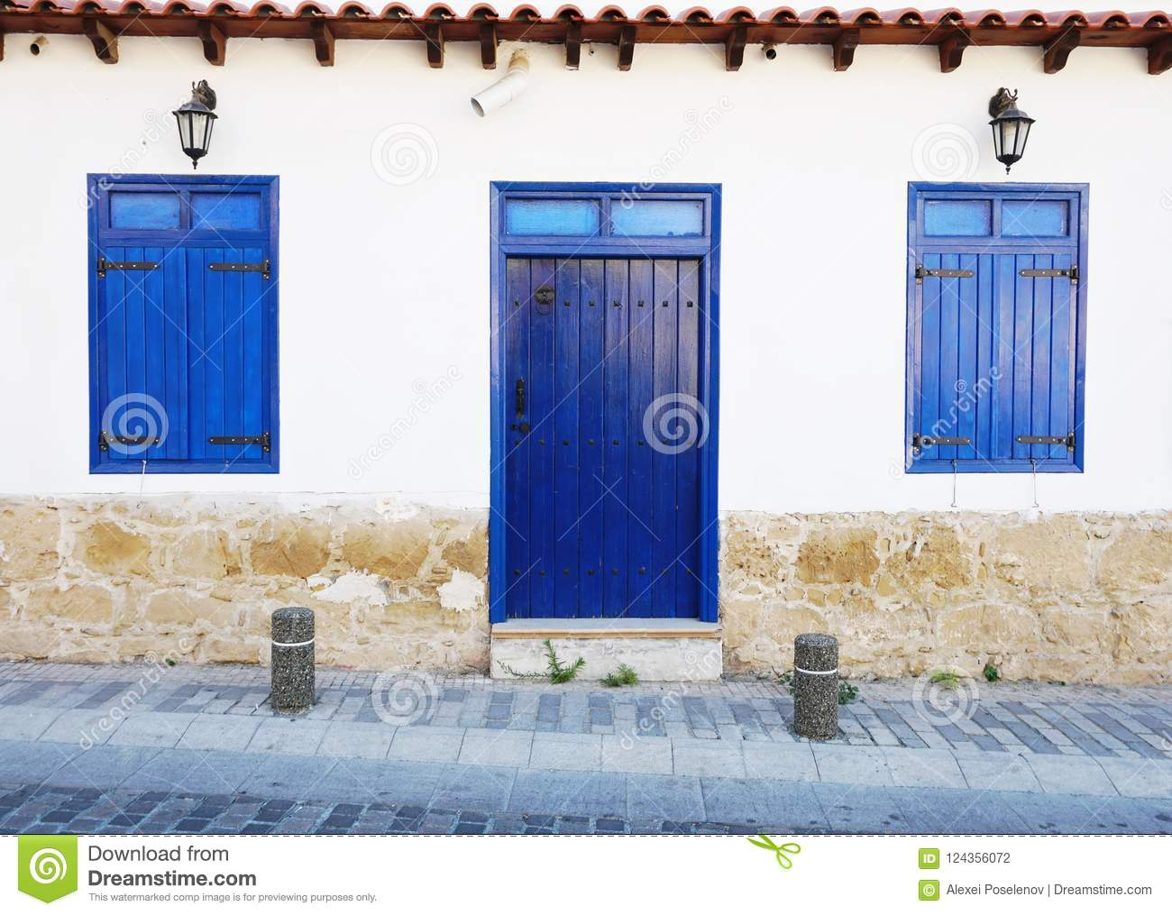 Closed Blue Front Door And Shutters On A White Wall Stock Photo