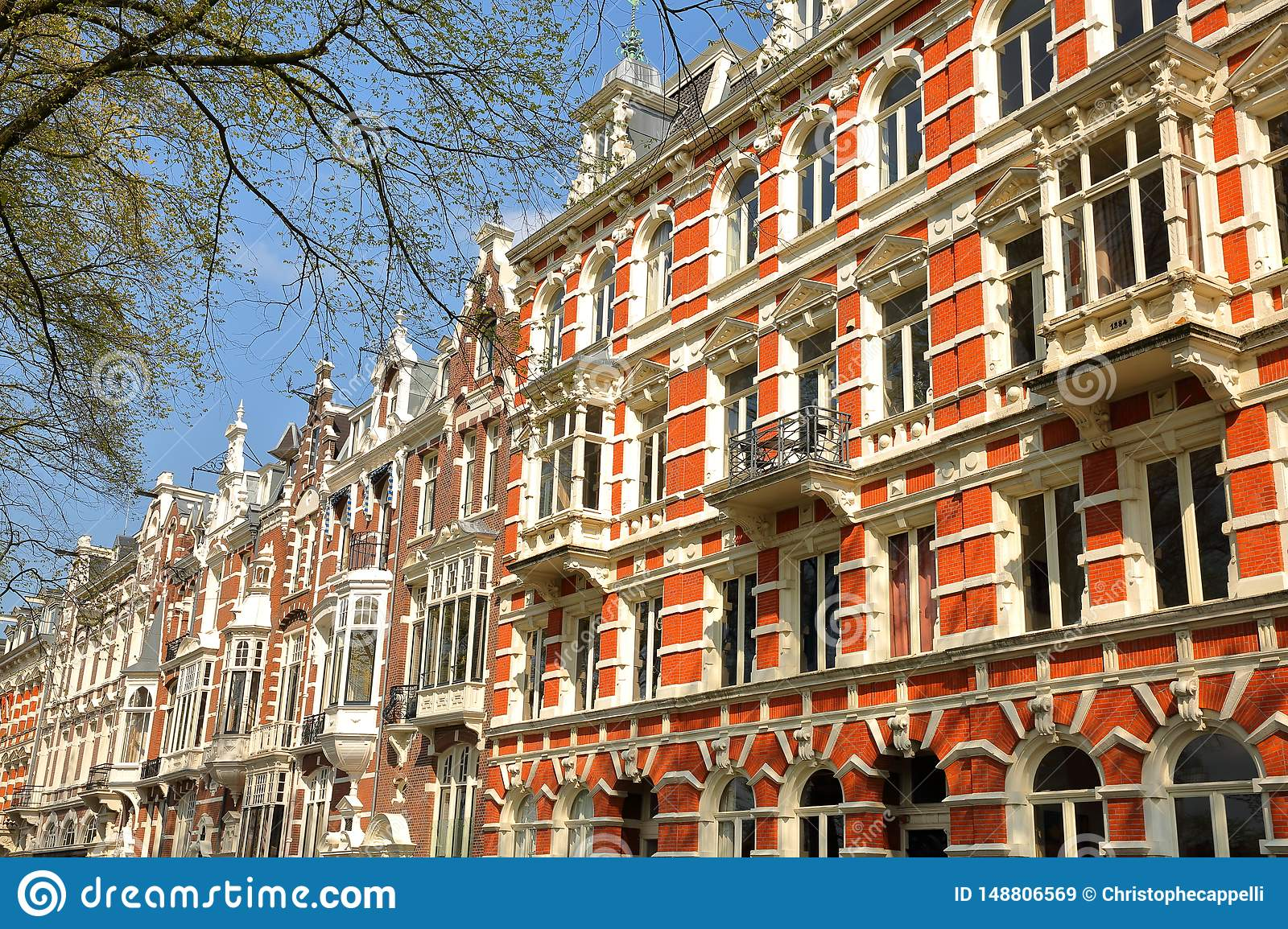 Traditional dutch old facades located on Weesperzijde Street along Amstel river, Amsterdam