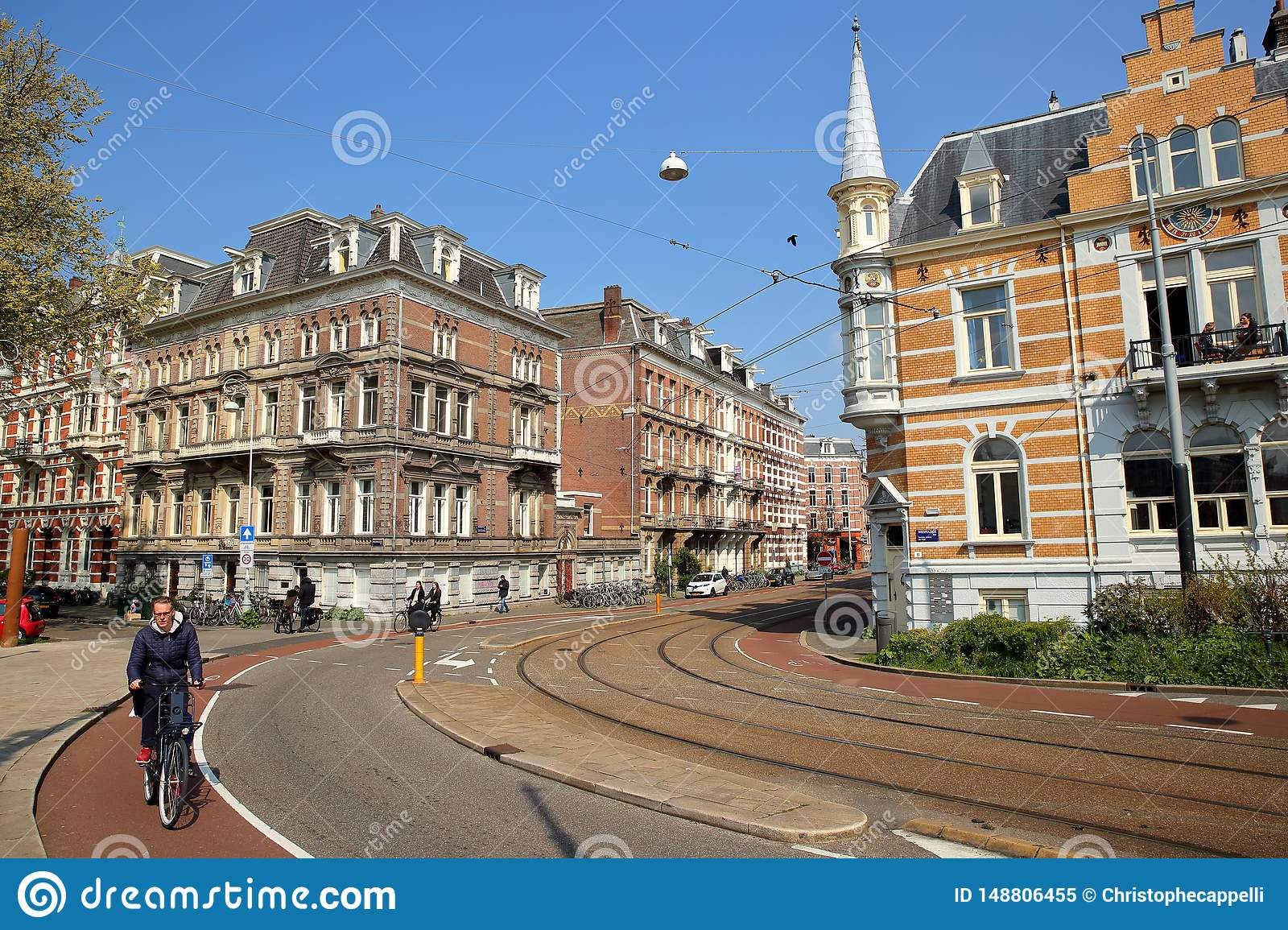 Traditional dutch old facades located on Weesperzijde Street along Amstel river, with people cycling in the foreground