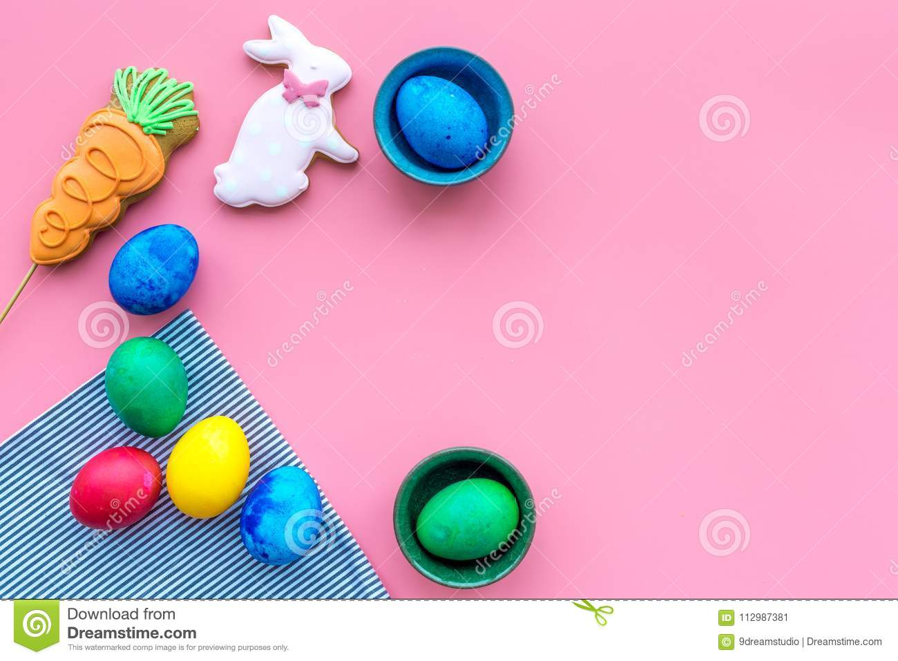 Traditional easter design with colorful eggs and rabbit and carrot cookie on pink background top view space for text