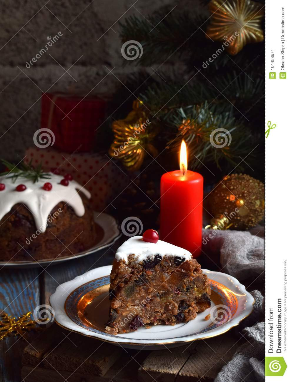 Traditional english Christmas steamed pudding with winter berries, dried fruits, nut in festive setting with Xmas tree and burning
