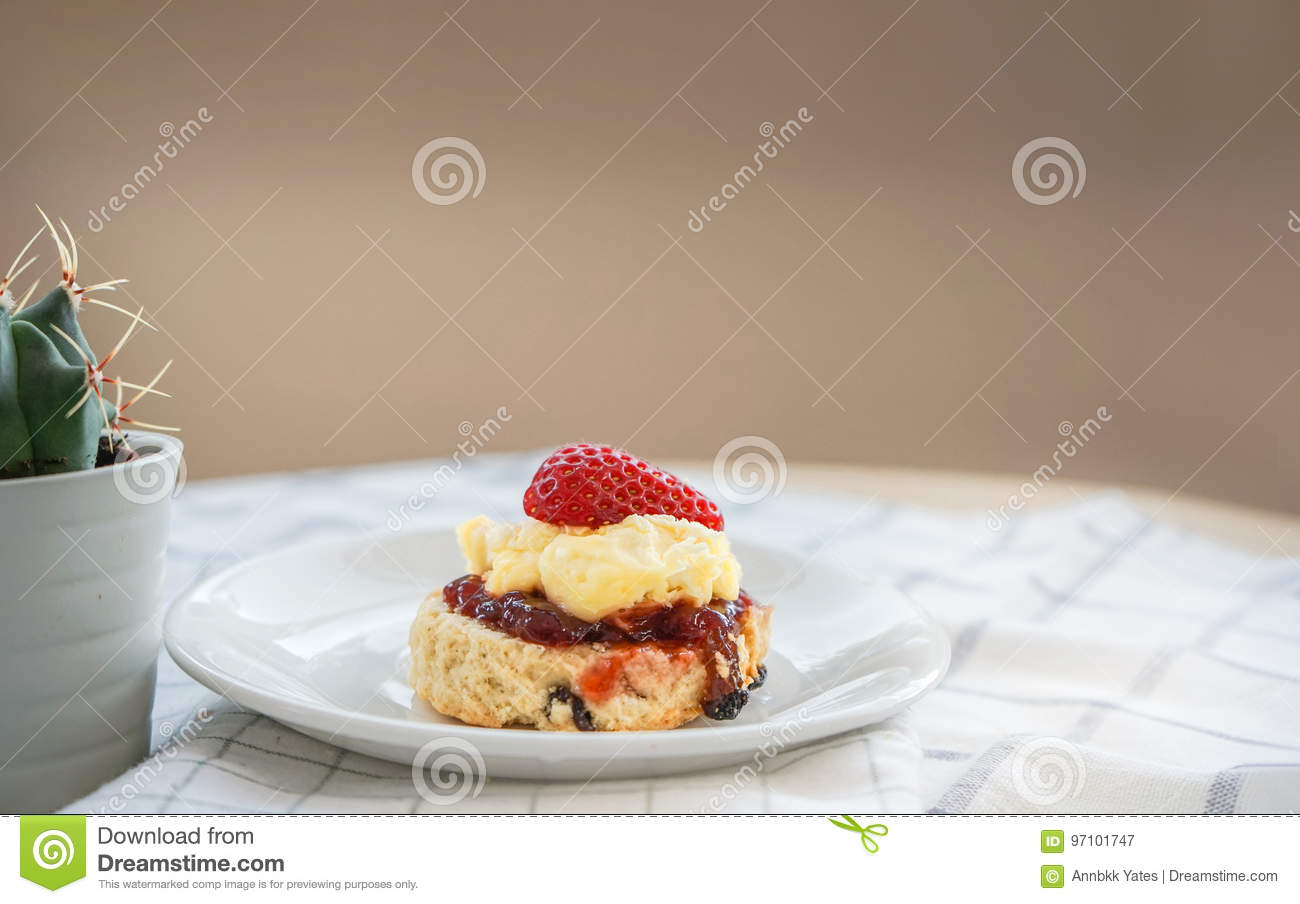 Traditional English Scones with strawberry jam and clotted cream topped with fresh strawberry