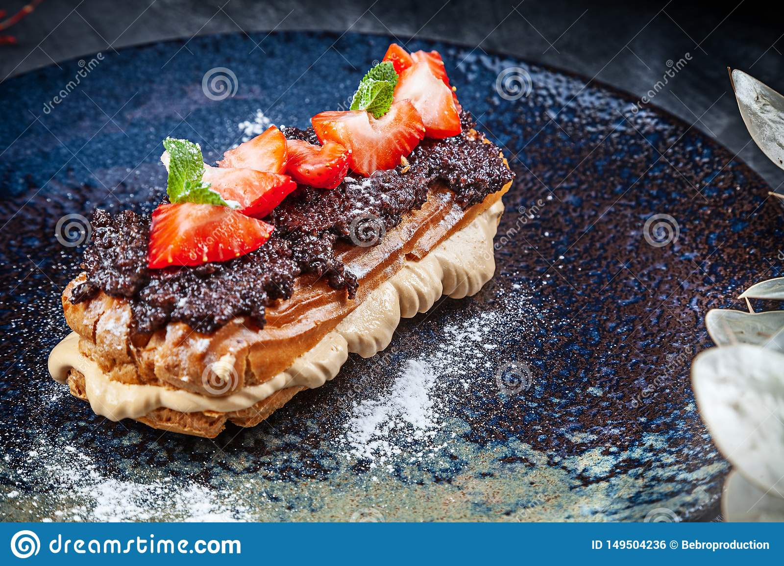Traditional french eclairs served on premium dark plate. Food for breakfast with copy space. Close up profitroles classic. eclair