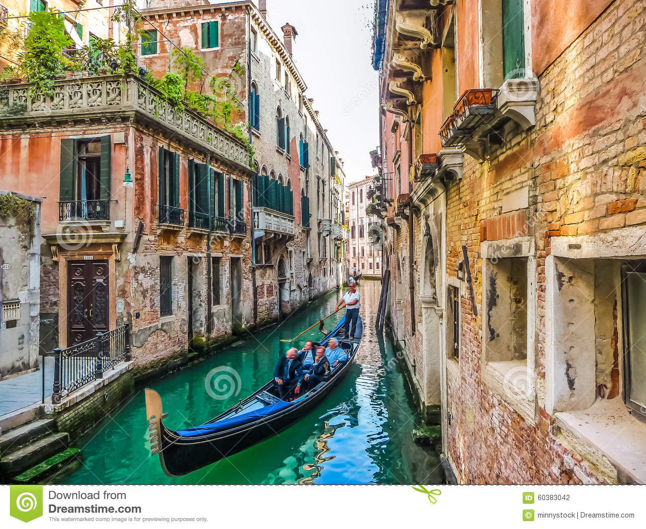 Traditional Gondolas on narrow canal between colorful houses, Venice, Italy