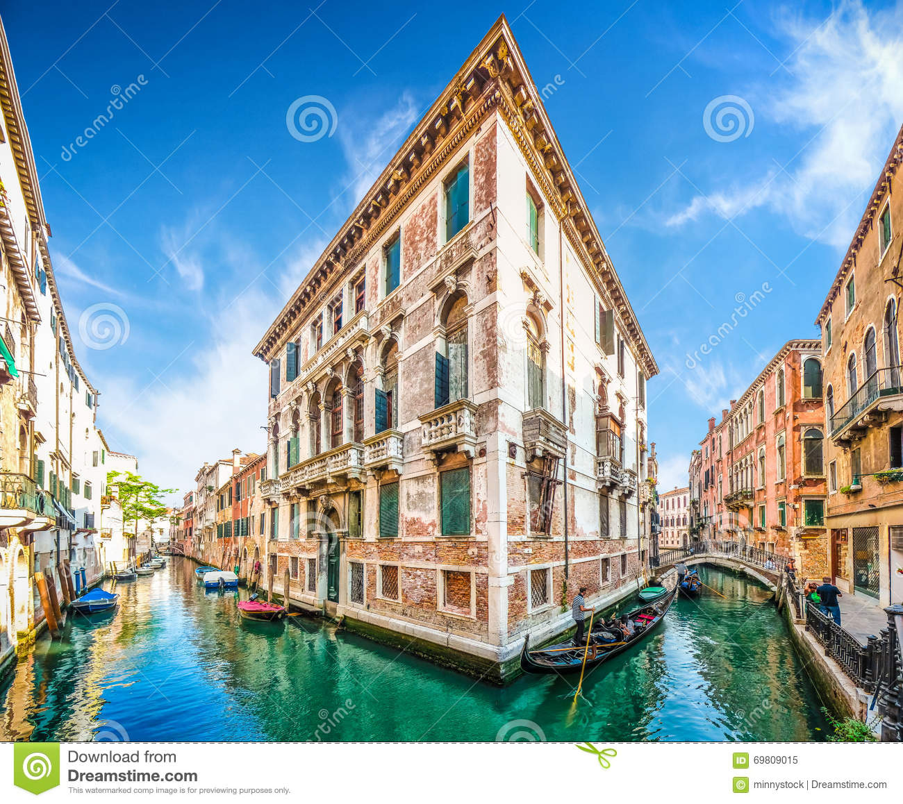 traditional gondolas on narrow canal between colorful