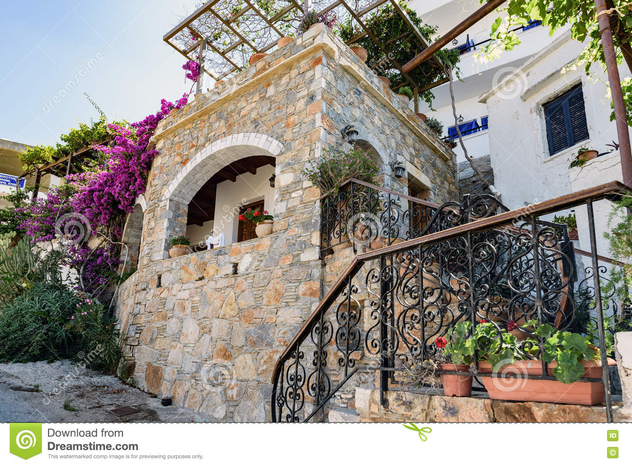 Traditional Greek House traditional greek stone house with purple bougainvillea flowers on