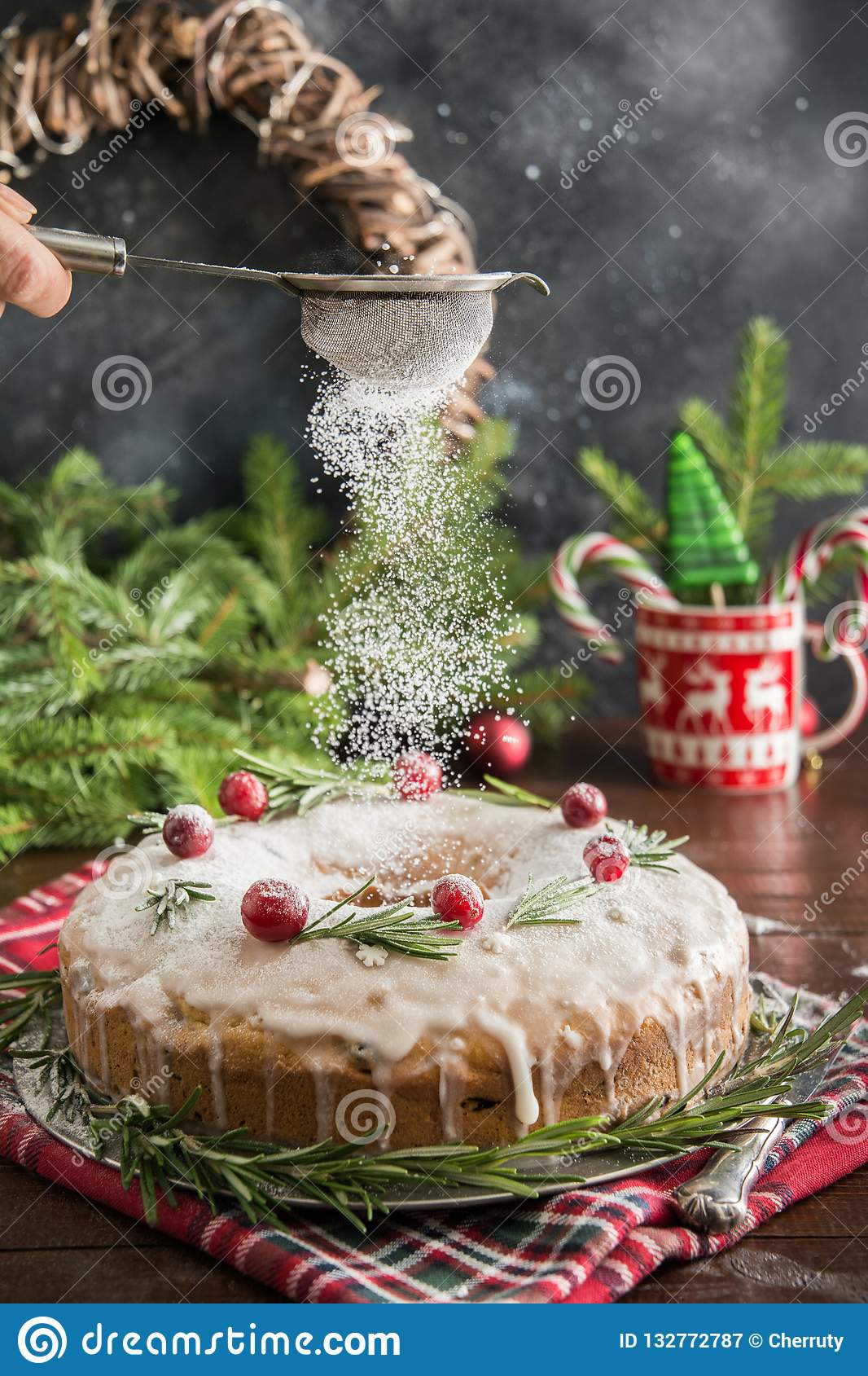 Traditional homemade Christmas cake with garnish cranberry and rosemary on decorative plate. Powdering with icing sugar.