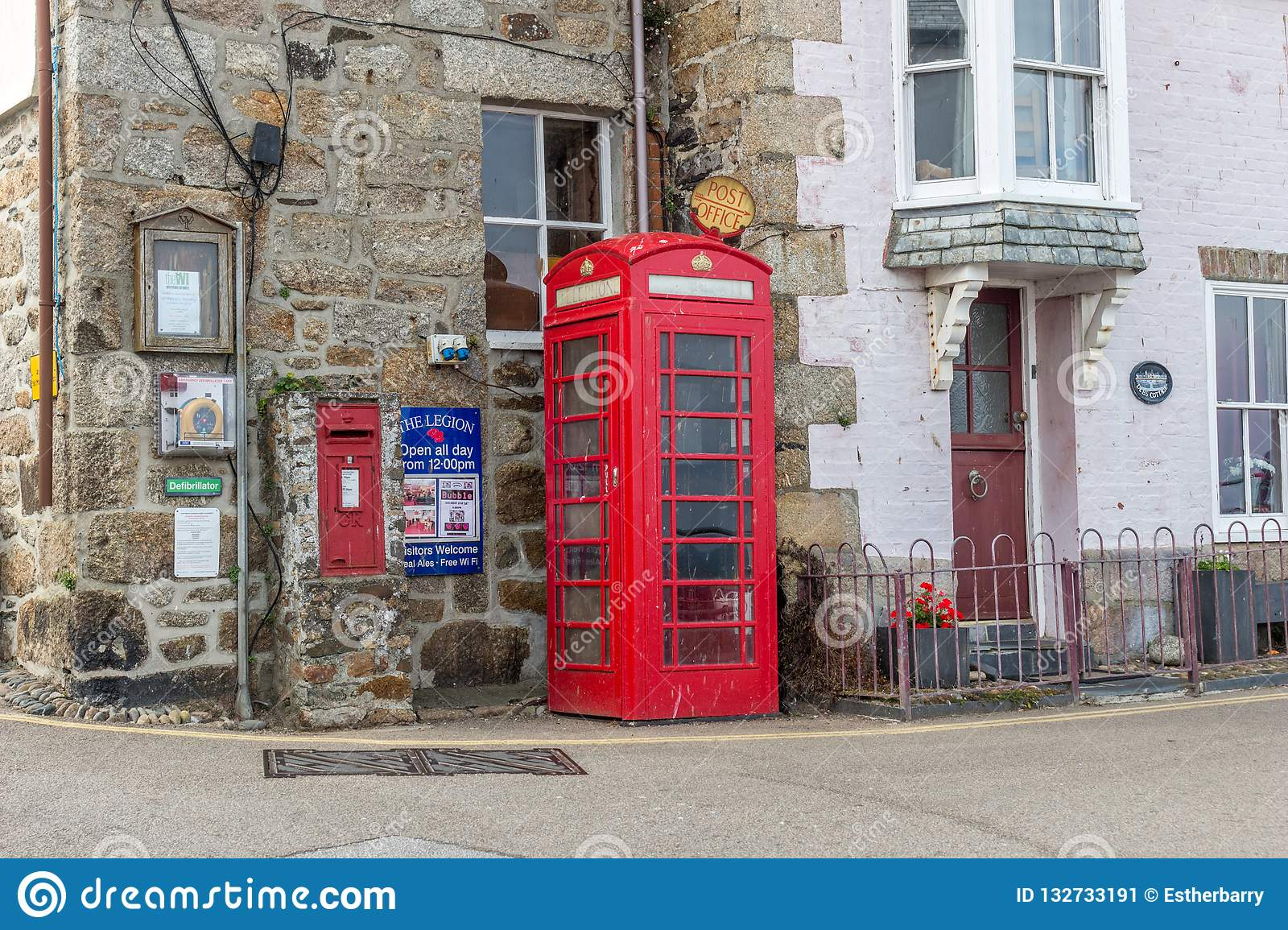 Traditional iconic British red telephone box in a street in Cornwall, England