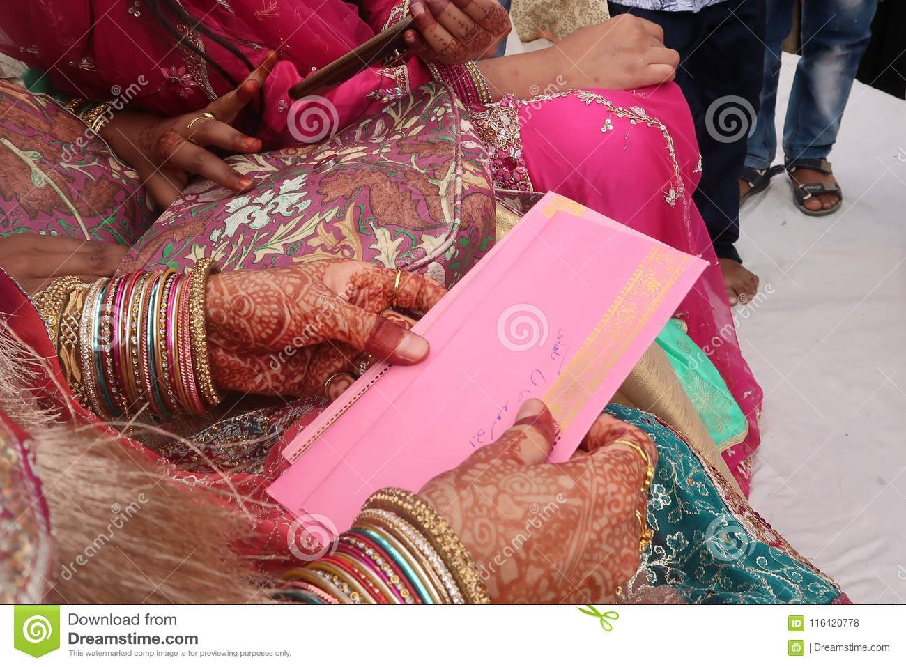 888ce4d883 Traditional indian wedding with red dress hands of indian bride with henna  doing traditional indian wedding mehndi with bangles and pink dress and  envelope ...
