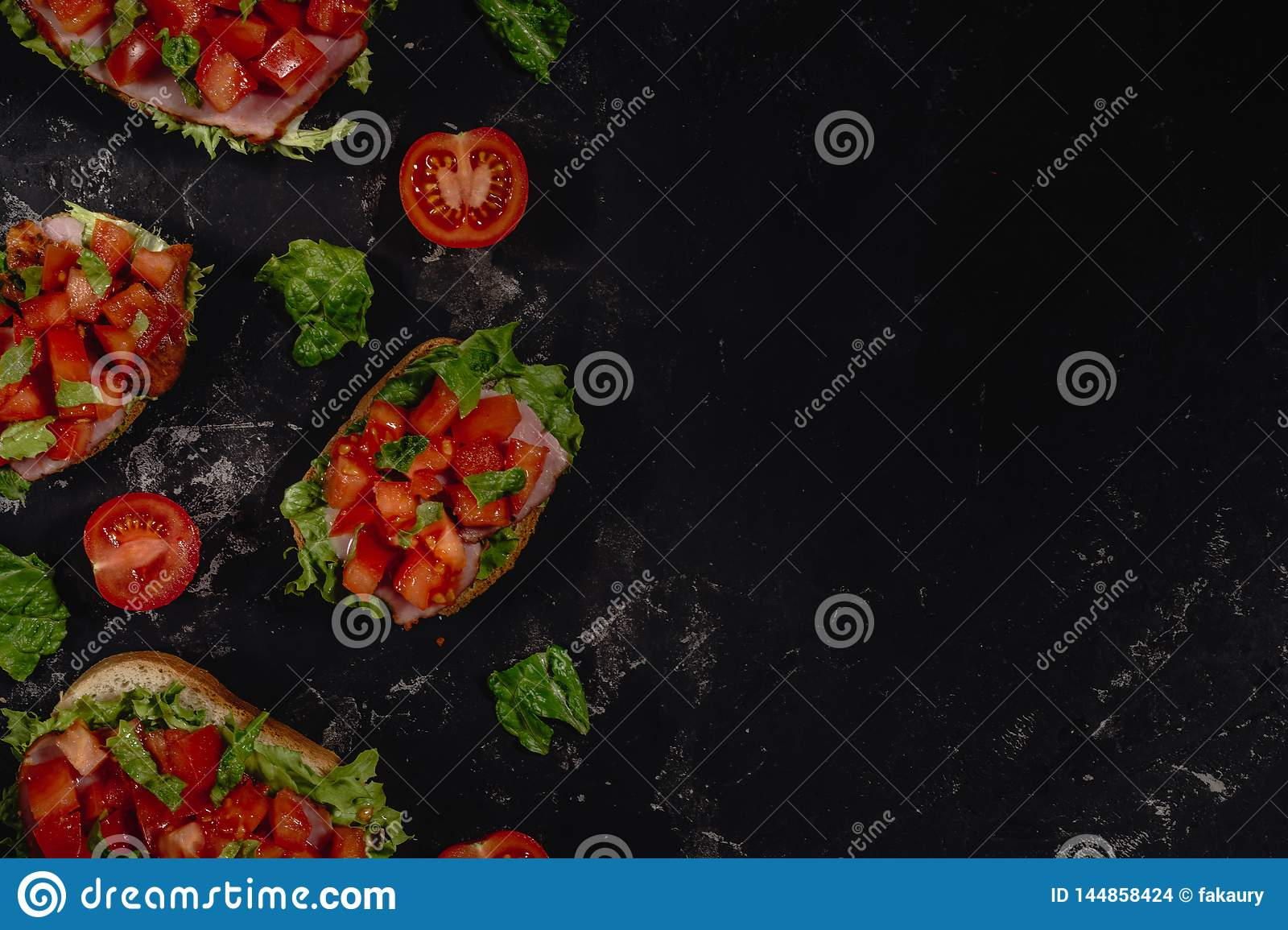 Traditional Italian Bruschetta with chopped tomatoes, mozzarella sauce, salad leaves and ham on a dark baton background.