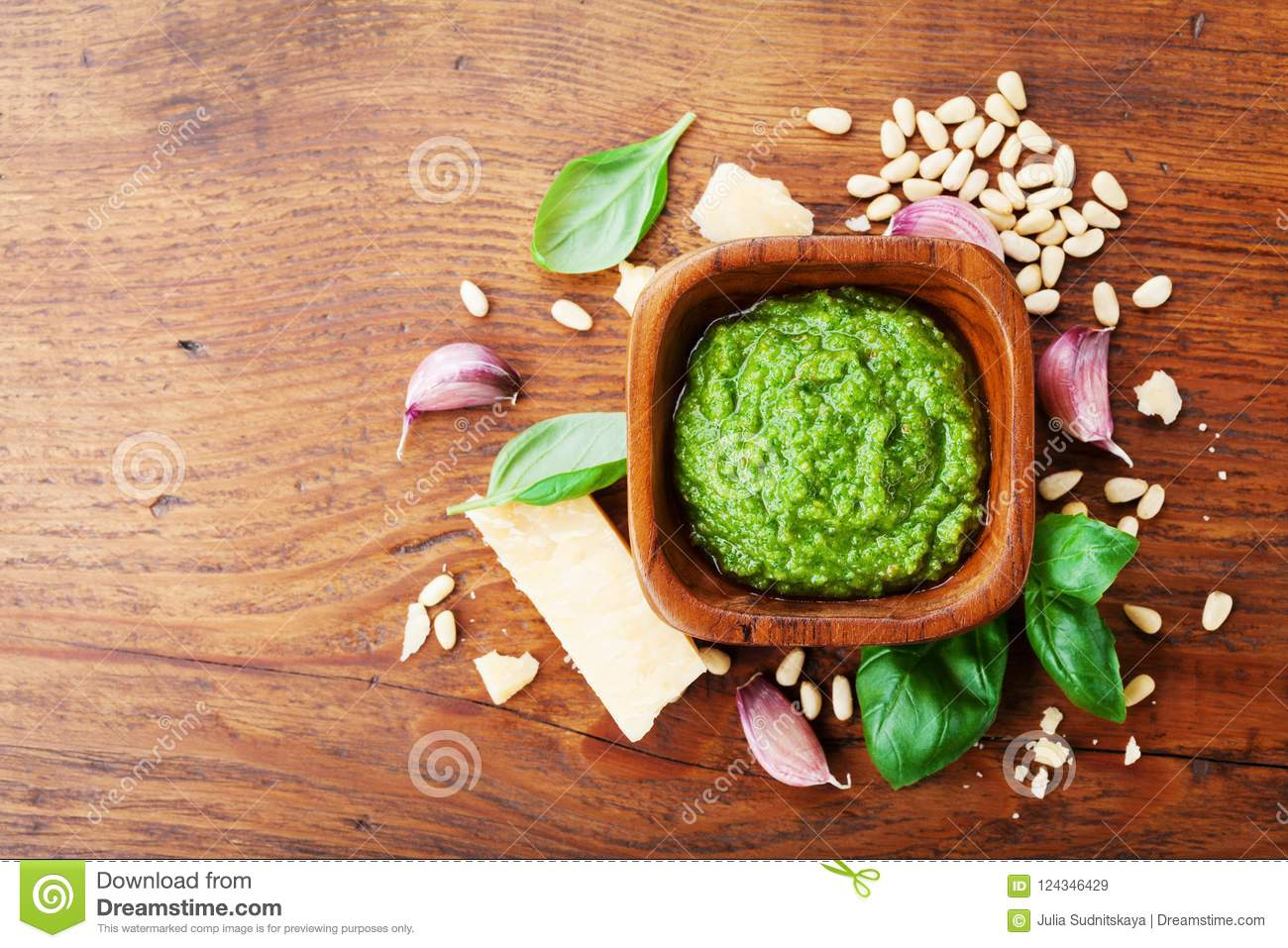 Traditional italian fresh pesto sauce with raw ingredients top view. Healthy and organic food.