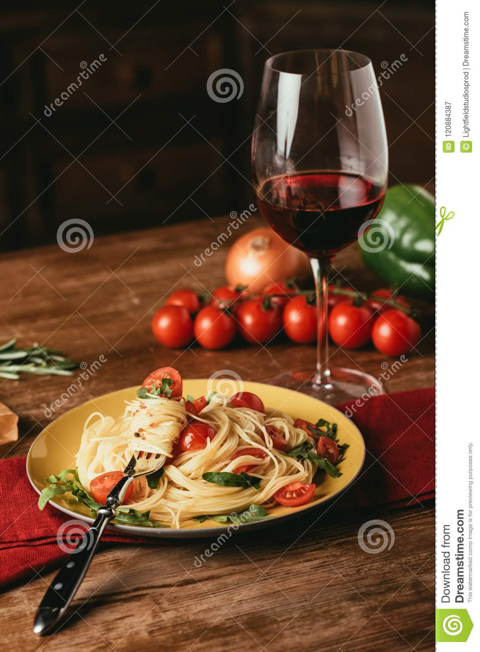 traditional italian pasta with tomatoes and arugula in plate and glass of