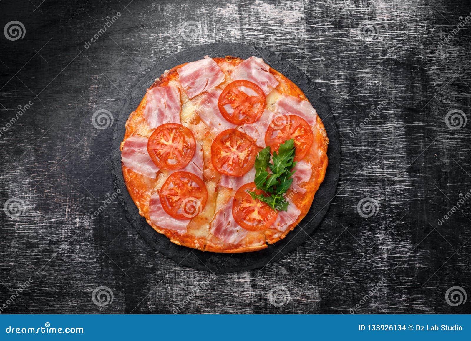 Traditional italian pizza with mozzarella cheese, ham, tomatoes