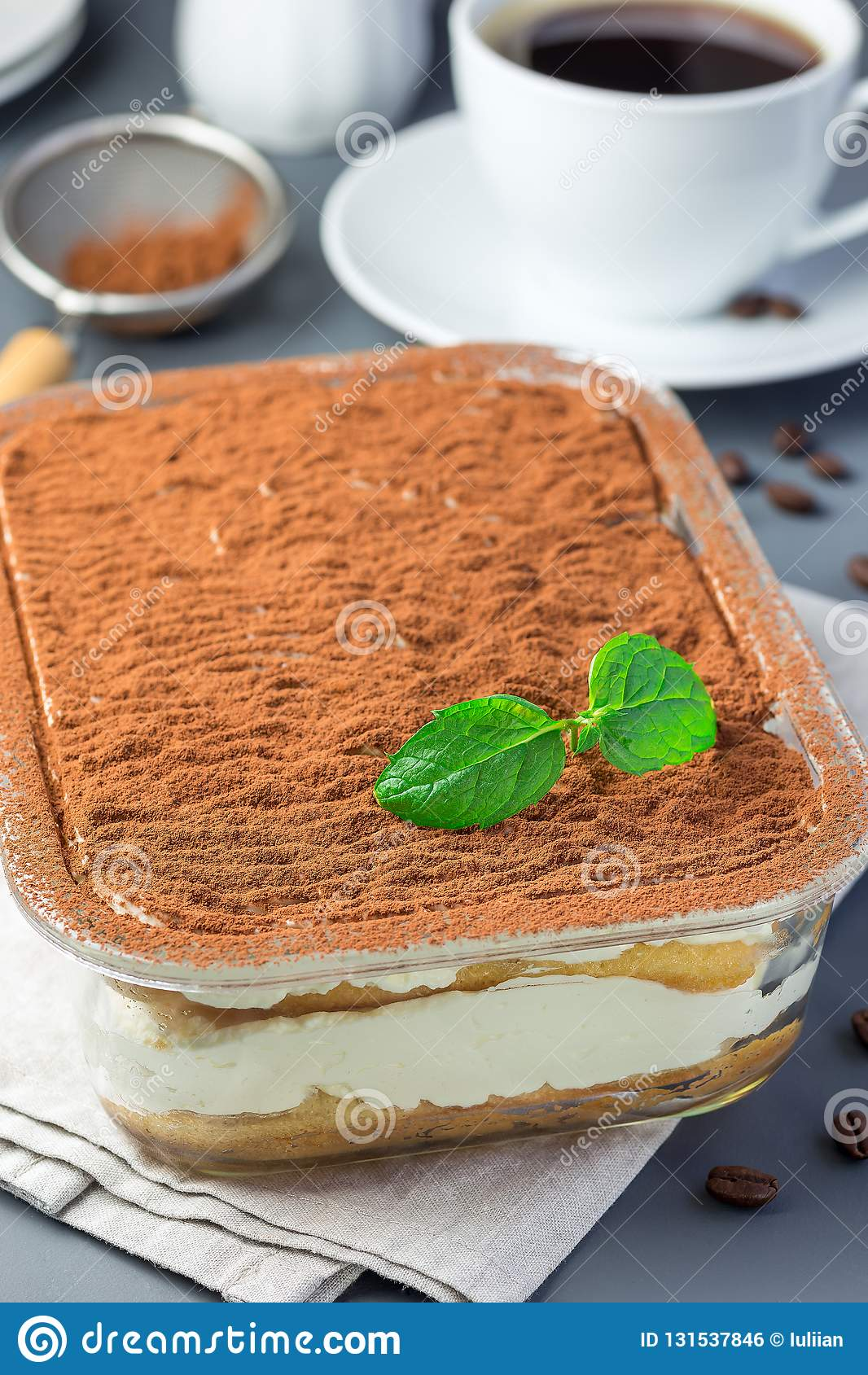 Traditional italian Tiramisu dessert cake in a glass form, decorated with cocoa powder and mint, with coffee cup, on a gray