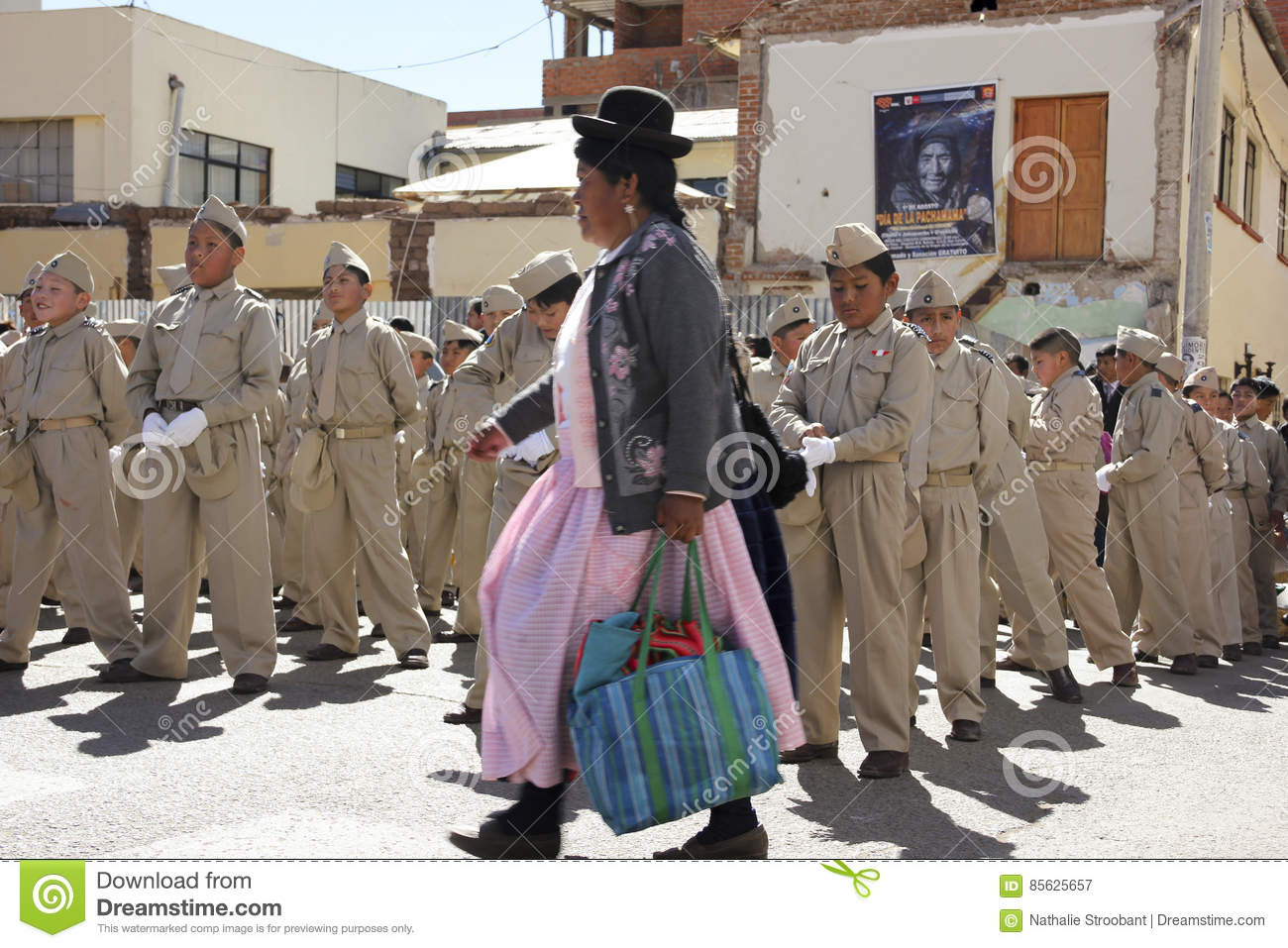 Traditional Peruvian woman passing by a group of schoolchildren