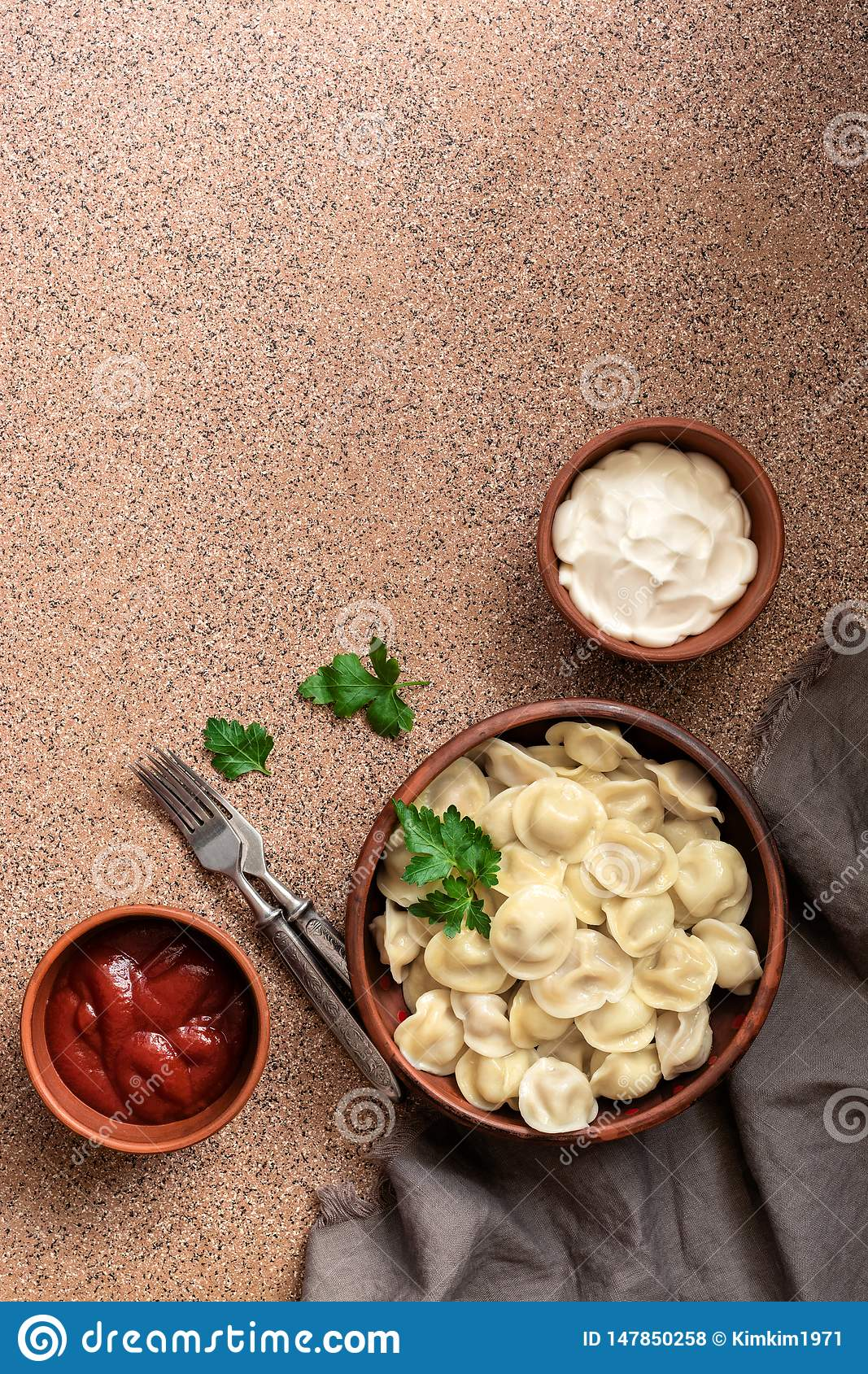 Traditional Russian food dumplings with meat served in a clay bowl with sour cream and tomato sauce. Top view, copy space