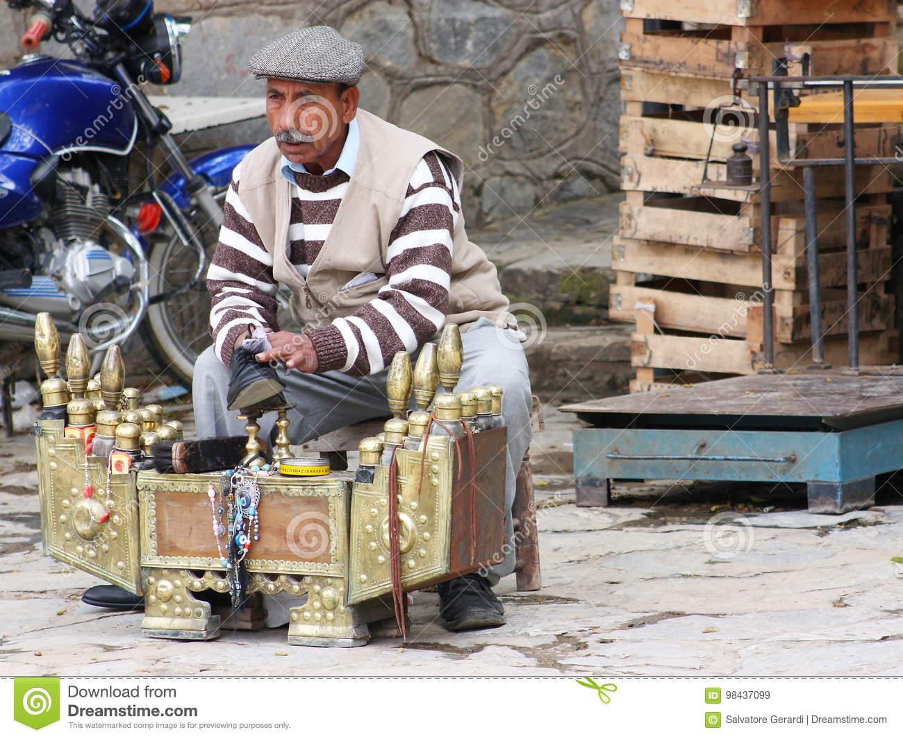 Traditional street shoe polisher cleaning a man`s shoe in Turkey