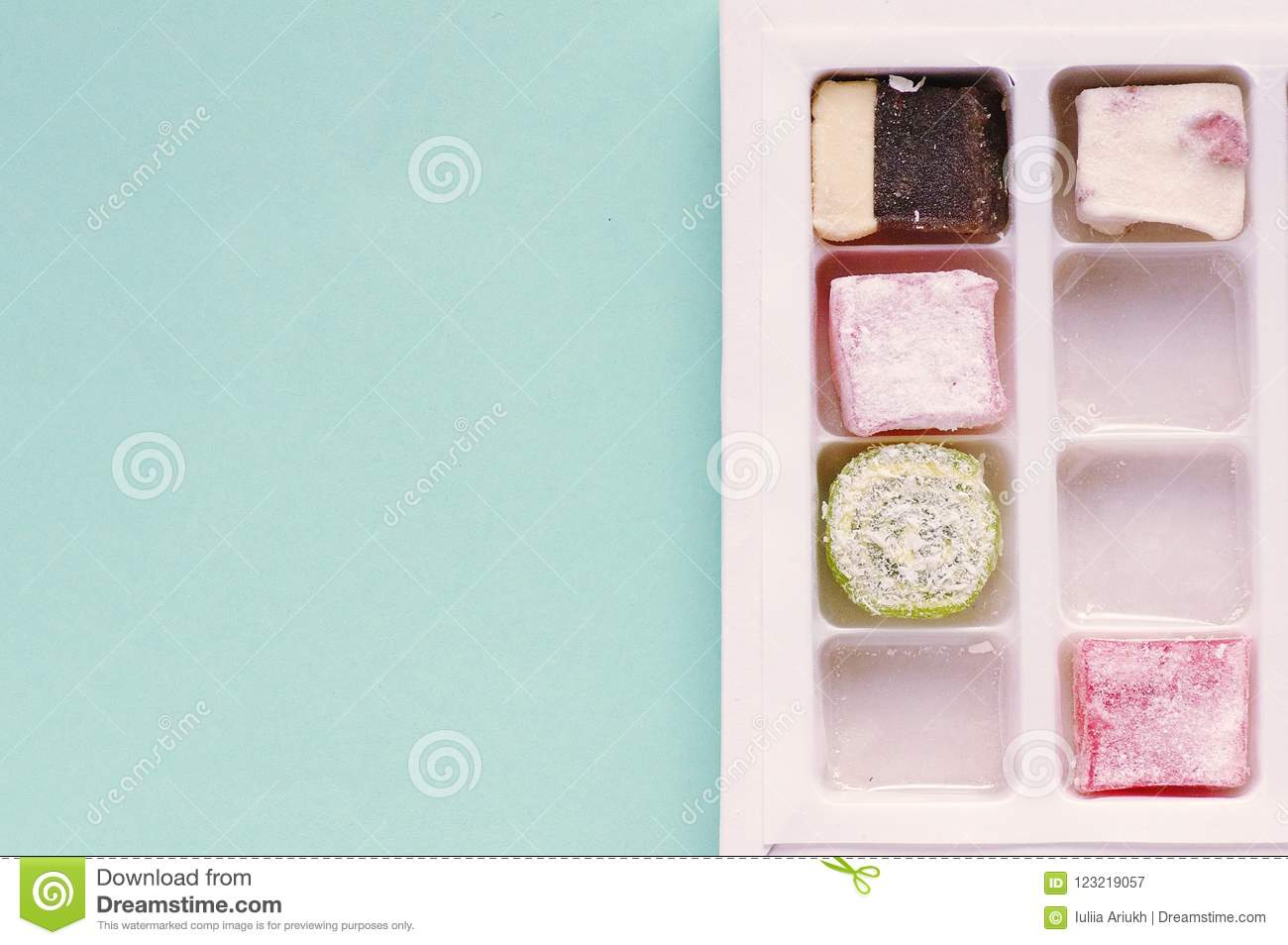 Traditional turkish delight on blue background. Arabic traditional dessert rahat lukum in a box.