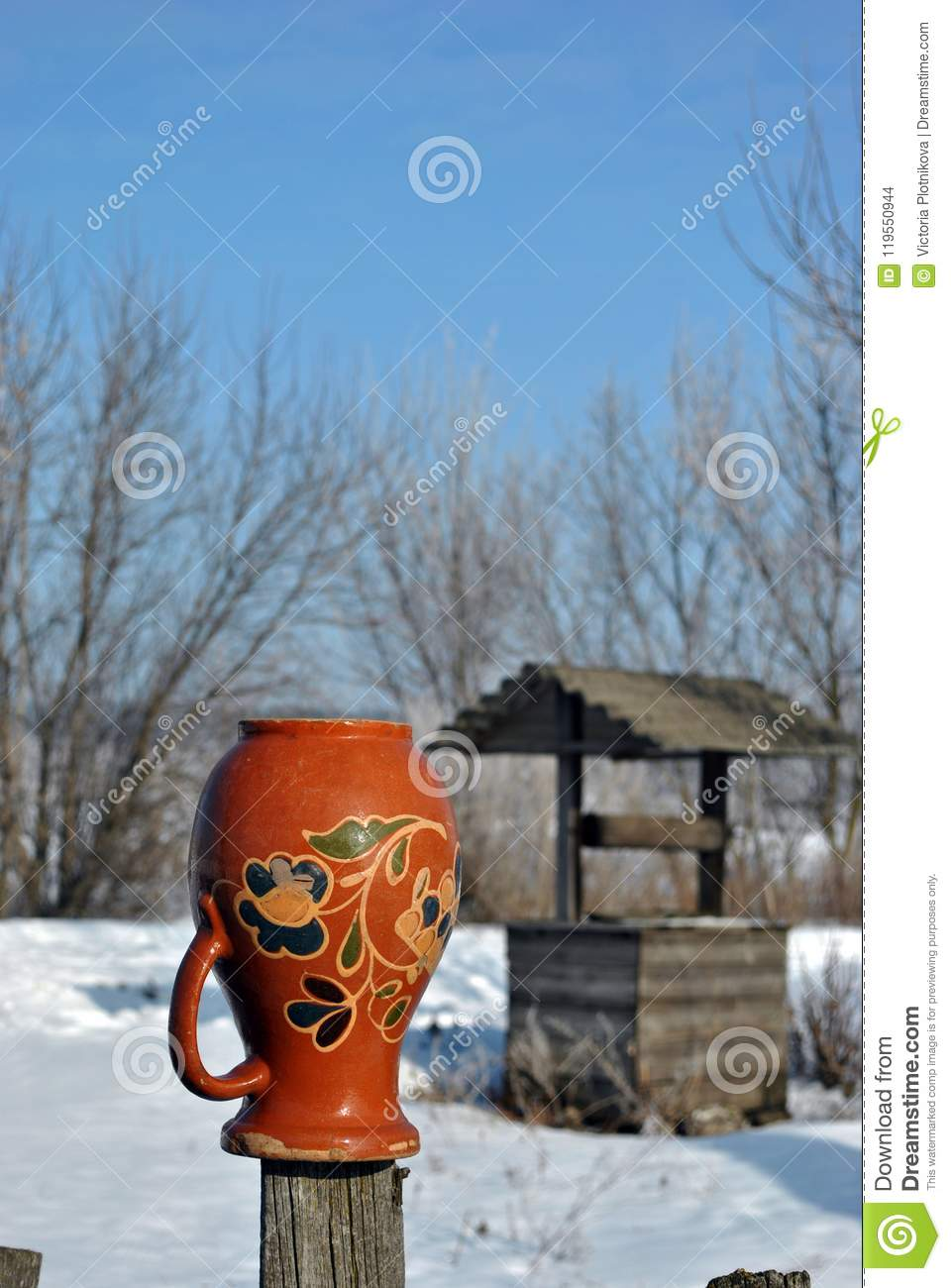 Traditional Ukrainian rural landscape with a wooden well and fence with hanging pitcher on it with Petrykivka folk painting