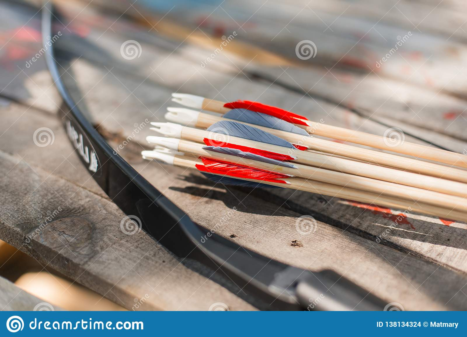 Traditional wooden arrows with feather fletching and a wooden bow in the background. Wooden archery homemade arrows with plastic nocks and natural feathers.