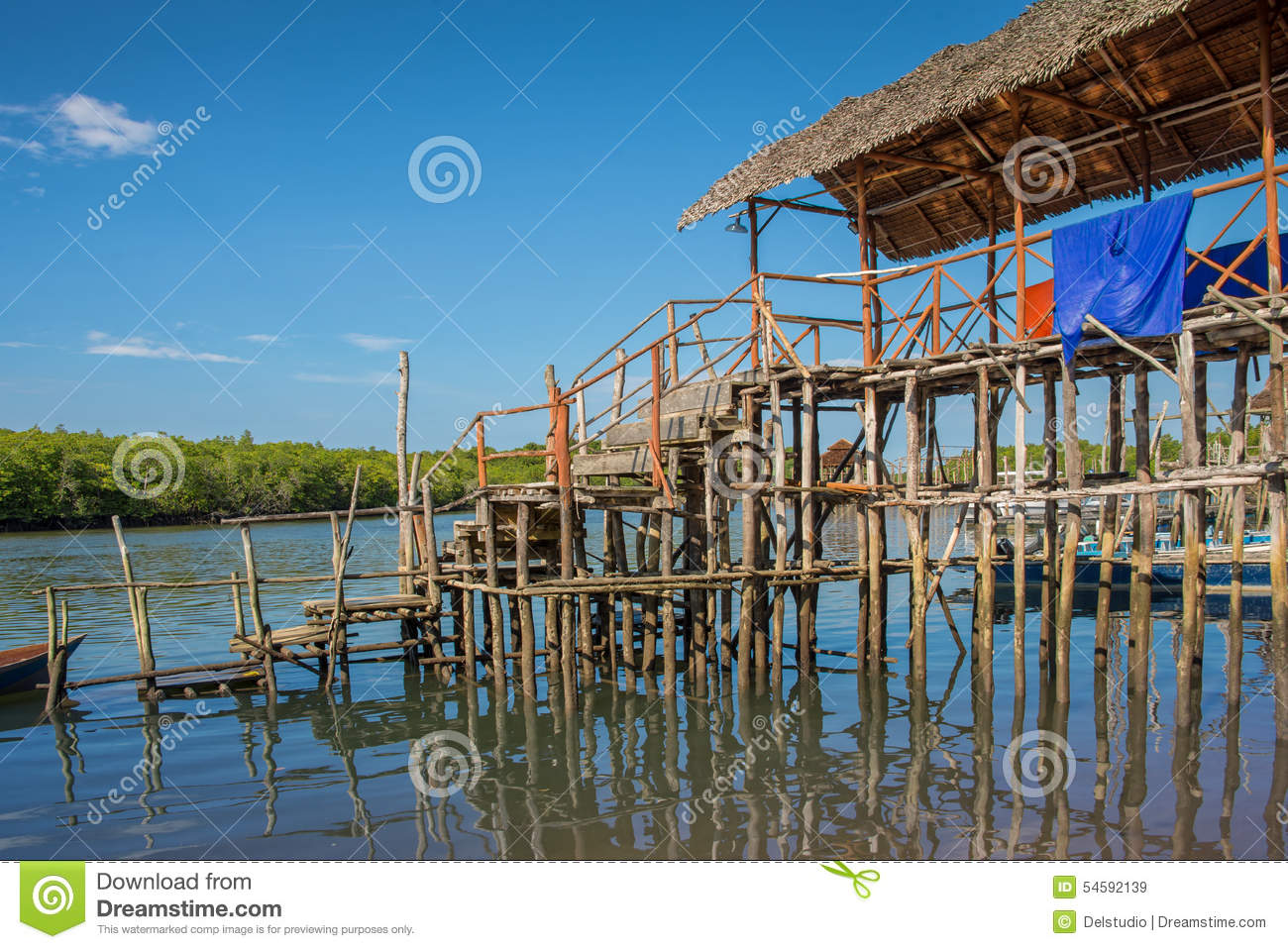Traditional stilts house and boat in water under blue sky stock photography - Household water treatment a traditional approach ...