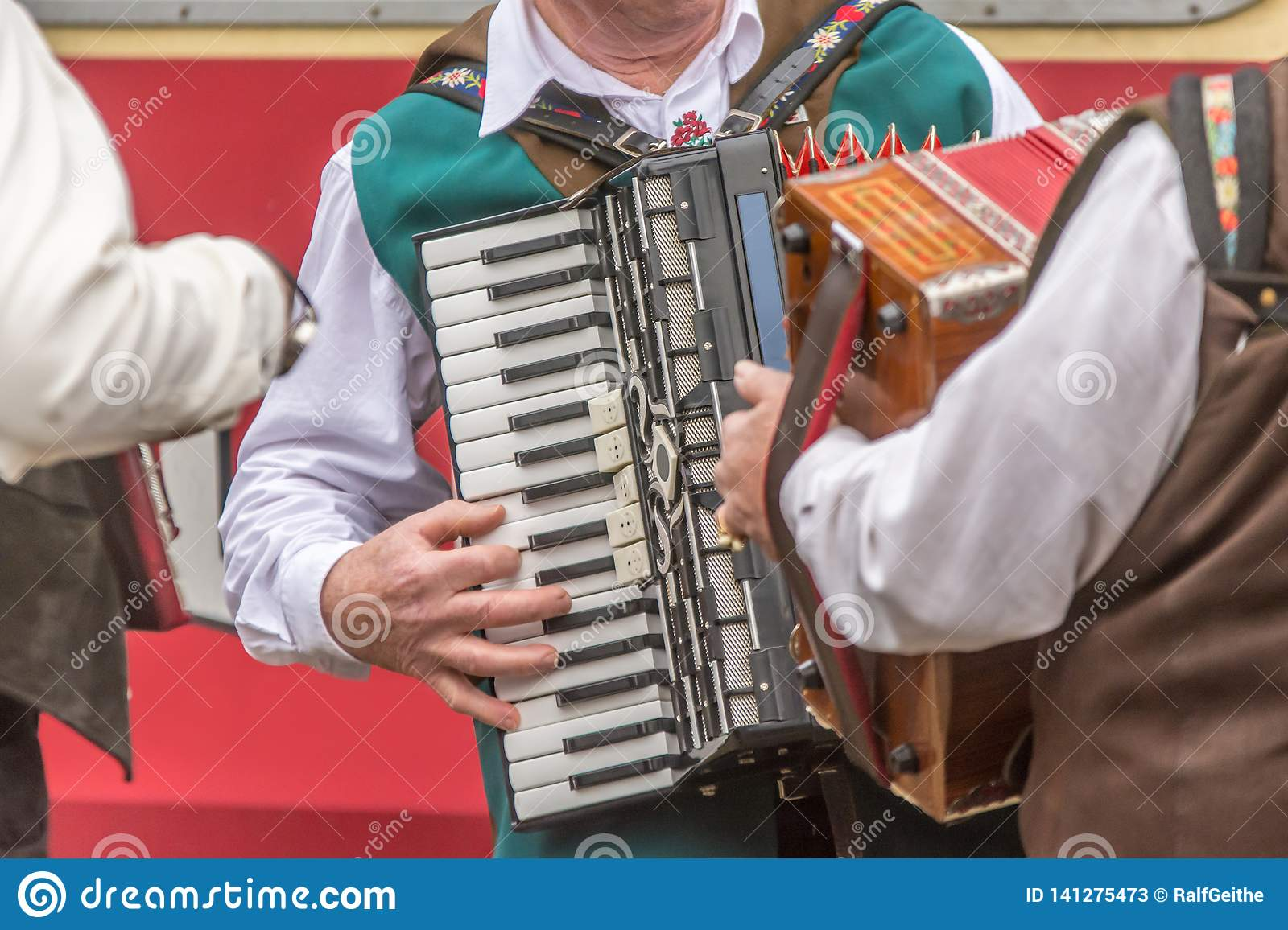 Several men in traditional clothes play the accordion