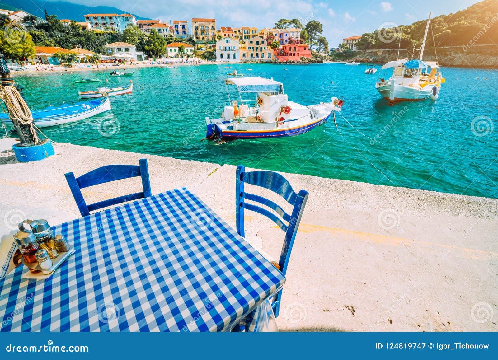 Traditioneel Grieks restaurant met blauwe en witte lijst en stoelen bij de overzeese kust van Assos-dorp Azuurblauw water