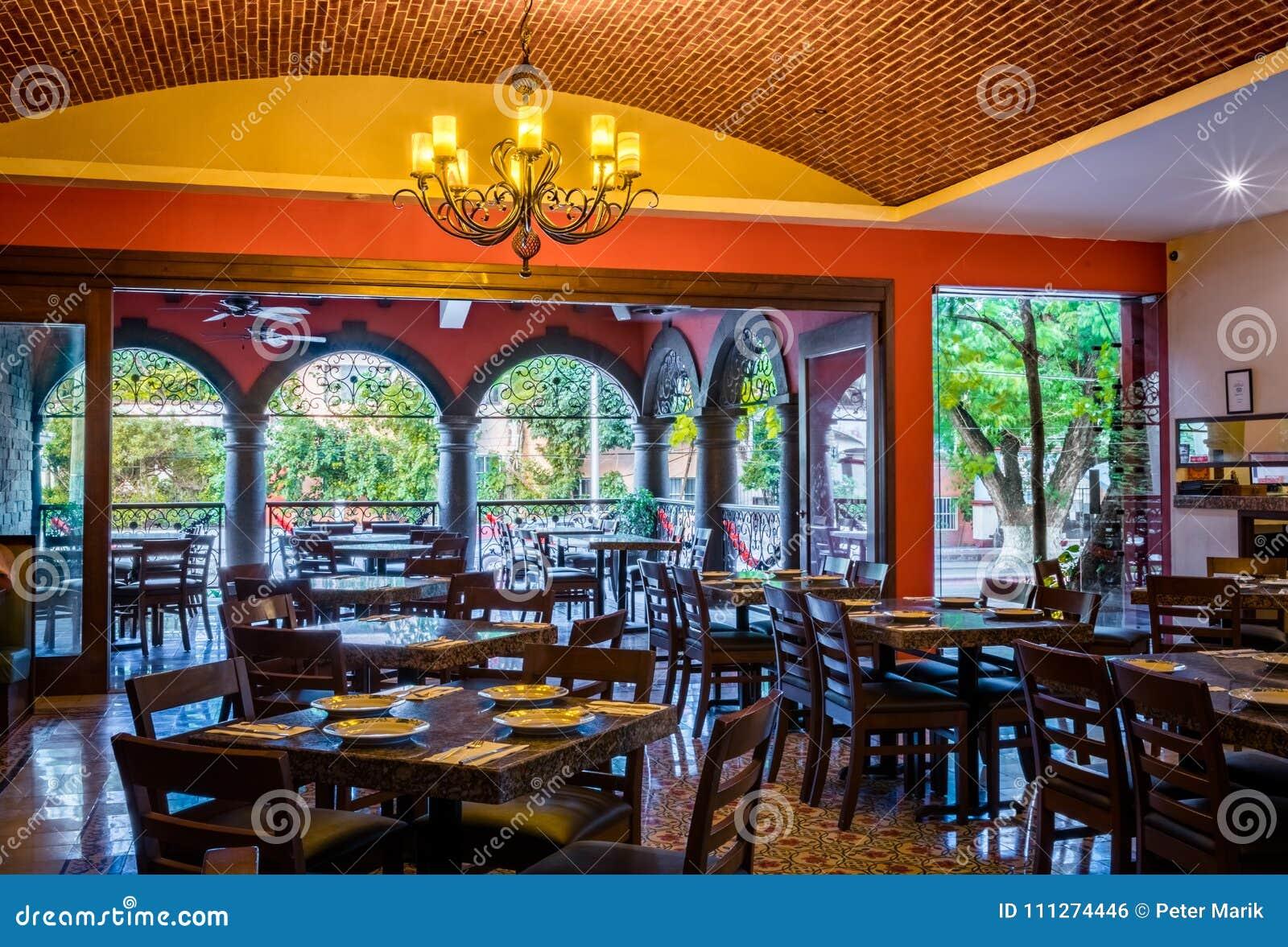 Traditioneel Mexicaans restaurantbinnenland met stoelen en lijsten, kroonluchter en baksteenplafond