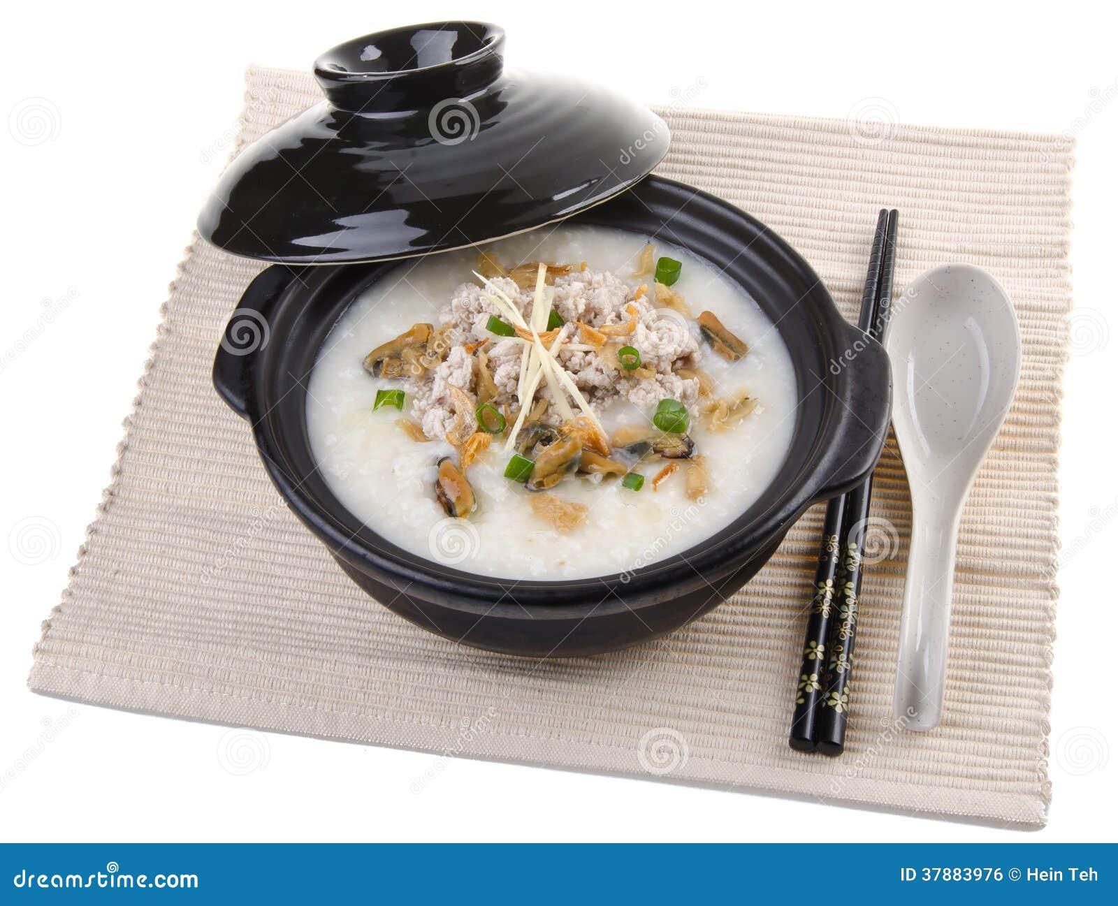 Traditionele Chinese die de rijsthaverbrij van de varkensvleeshavermoutpap in claypot wordt gediend