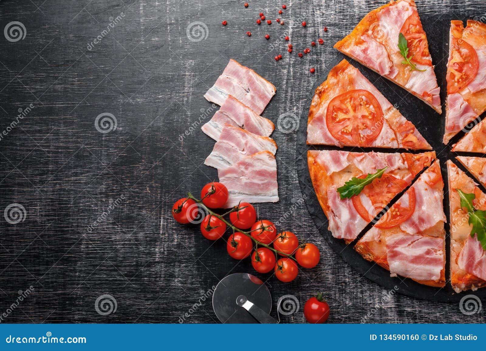 Traditionele Italiaanse pizza met mozarellakaas, ham, tomaten, peper, pepperoniskruiden en verse rucola