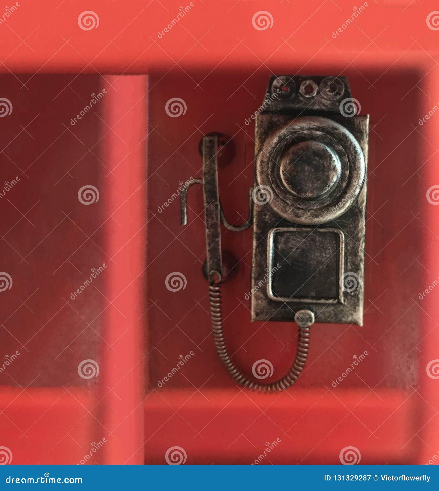 Traditionele klassieke rode telefoondoos, waarin de conventionele roterende telefoon van de muurwijzerplaat in bijlage is, klaar
