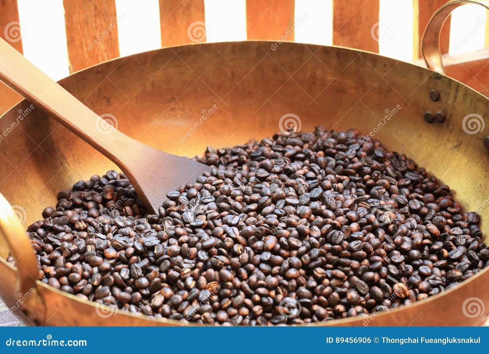 Traditionele koffiebonen die in metaalbassin roosteren met spatel