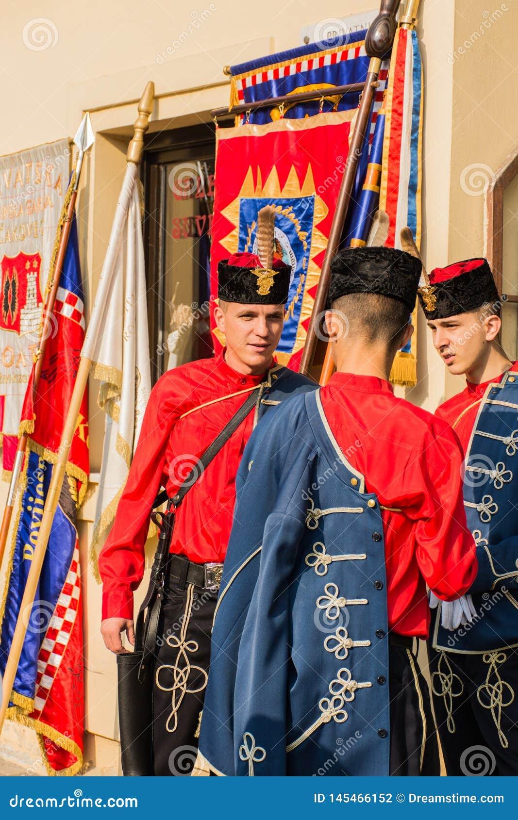 Traditionele militairen die op parade wachten die traditionele uniformen en hoeden draagt