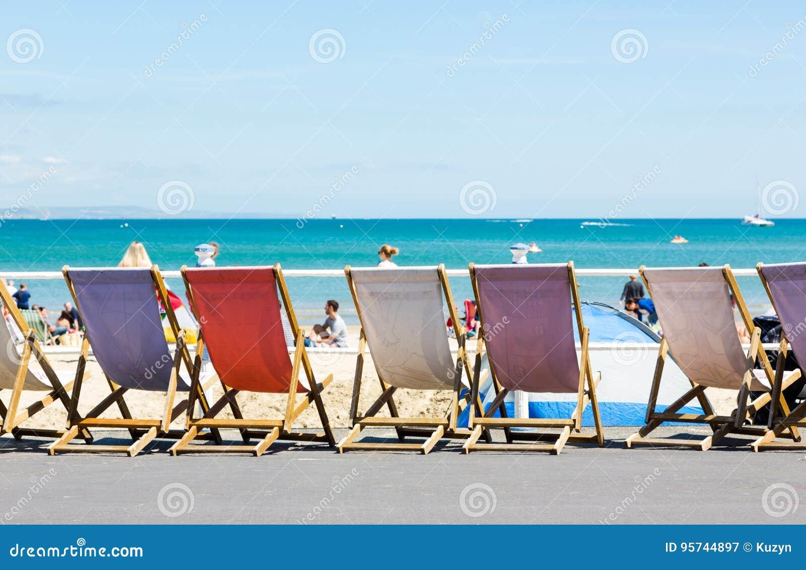 Traditionele oude manier houten ligstoelen langs promenade in Weymouth