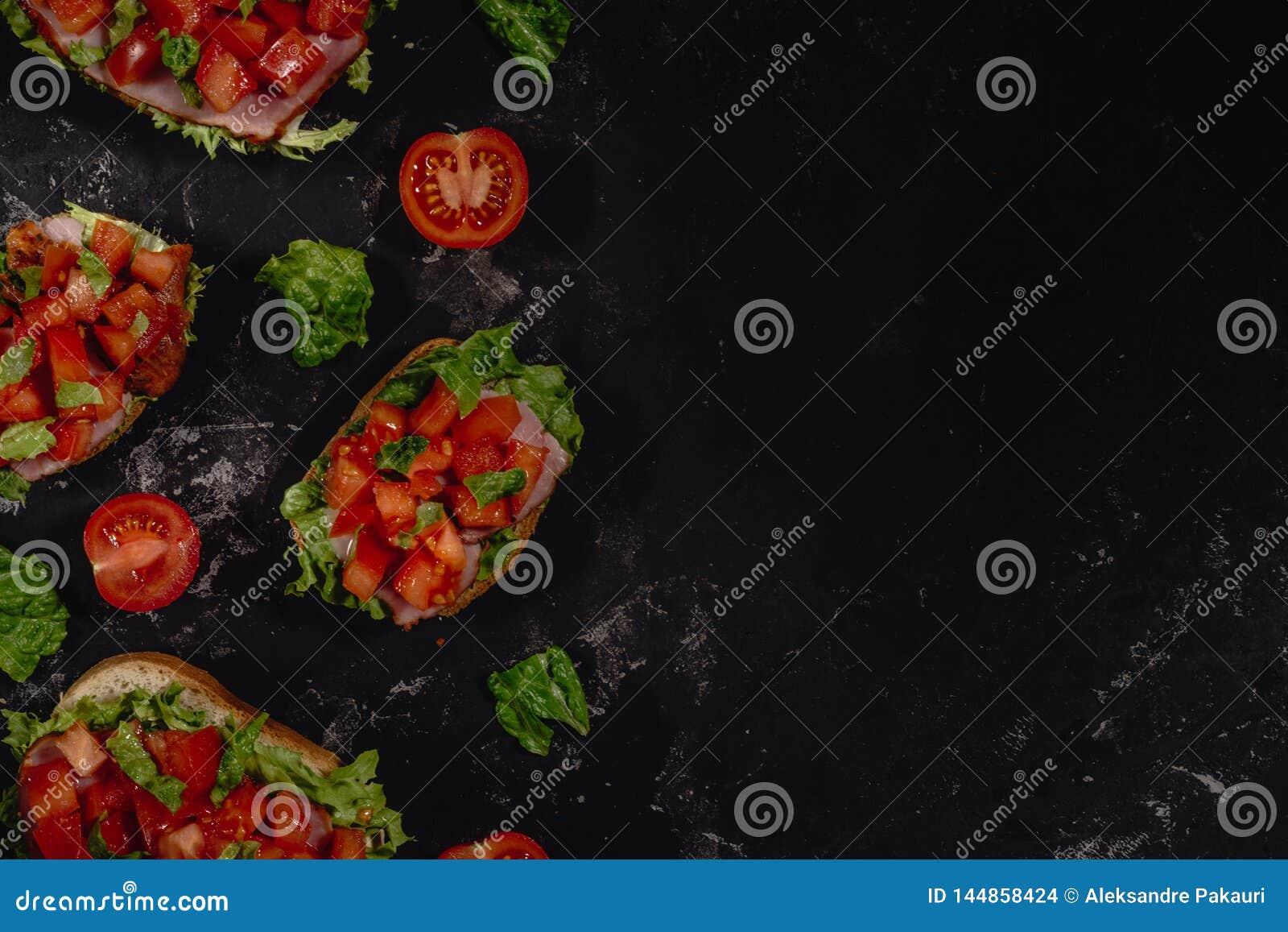 Traditionell italienare Bruschetta med huggen av tomater, mozzarellas?s, salladsidor och skinka p? en m?rk taktpinnebakgrund