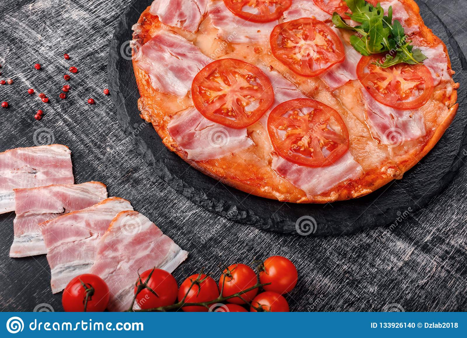Traditionell italiensk pizza med mozzarellaost, skinka, tomater