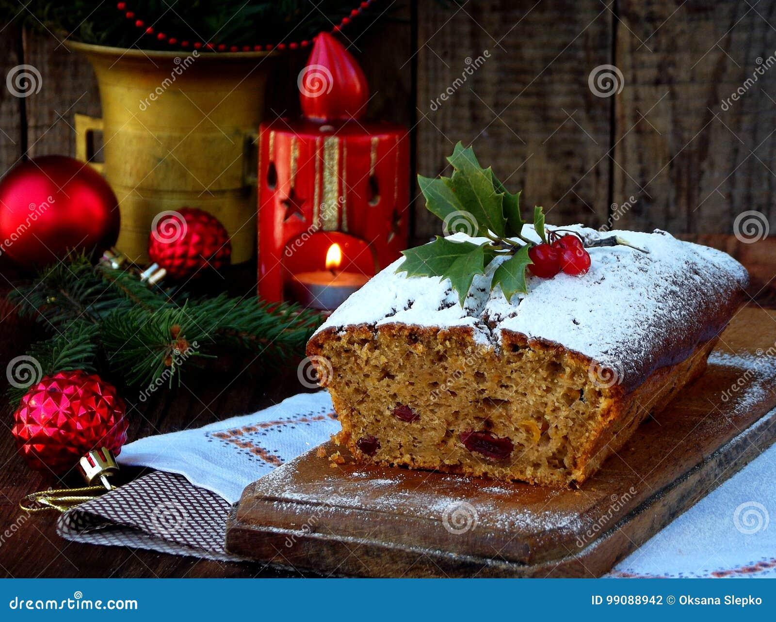 Traditionell jul bär frukt kakan som dekoreras med pudrade socker- och mas-garneringar, stearinljus kopiera avstånd Lantlig stil