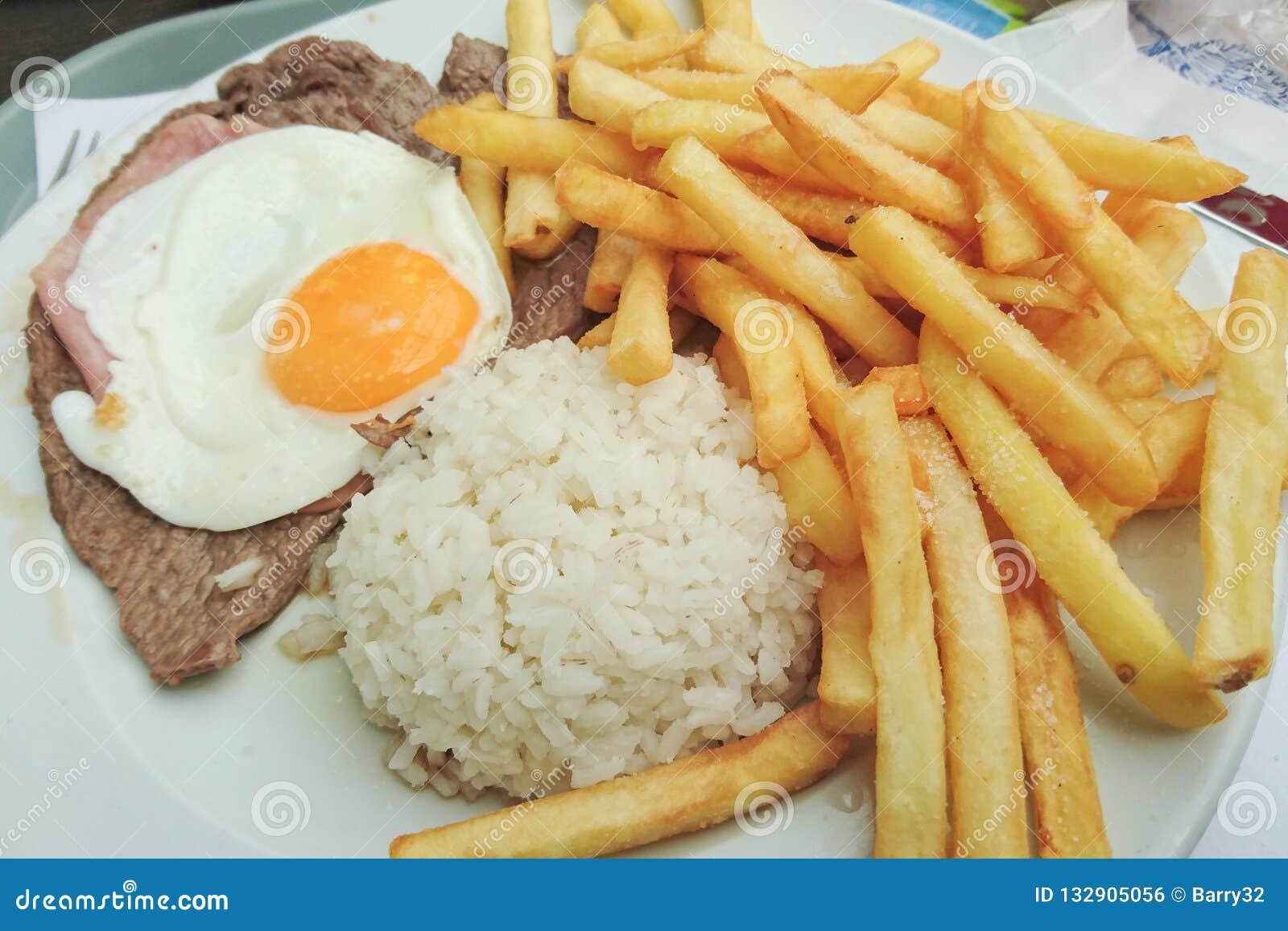 Traditionell portugisisk mat Prego ingen Prato med ris, chiper, ägget och nötkött