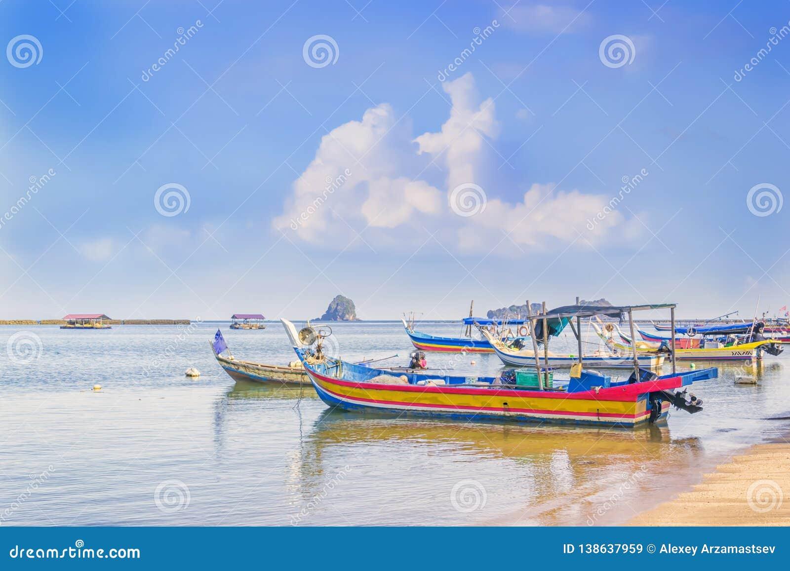 Traditionella asiatiska fiskebåtar med förtjänar parkerat av kusten för gående fiska på en bakgrund för blå himmel med moln