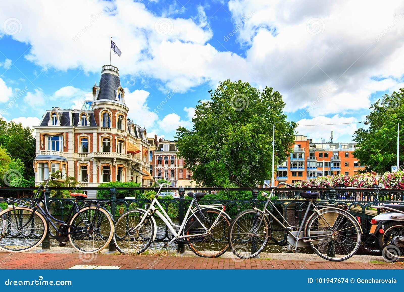 Traditionella holländarecyklar som parkeras längs gatan på Museumbrug broar över kanalen Amsterdam i sommar, Nederländerna, Europ