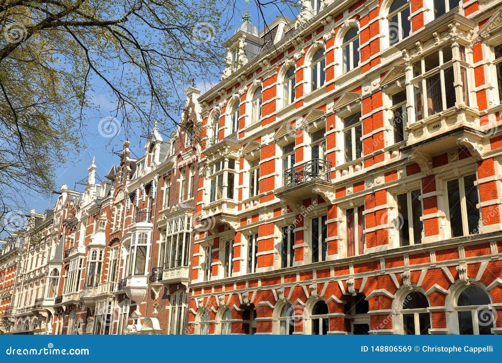 Traditionella holl?ndska gamla fasader som lokaliseras p? den Weesperzijde gatan l?ngs den Amstel floden, Amsterdam