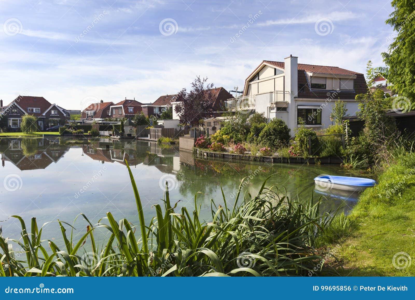 Traditionella hus runt om ett damm i Nederländerna