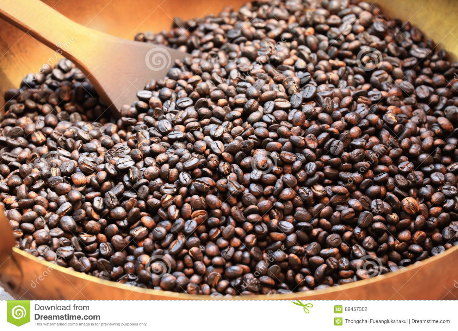 Traditionella kaffebönor som grillar i metallhandfat med spateln
