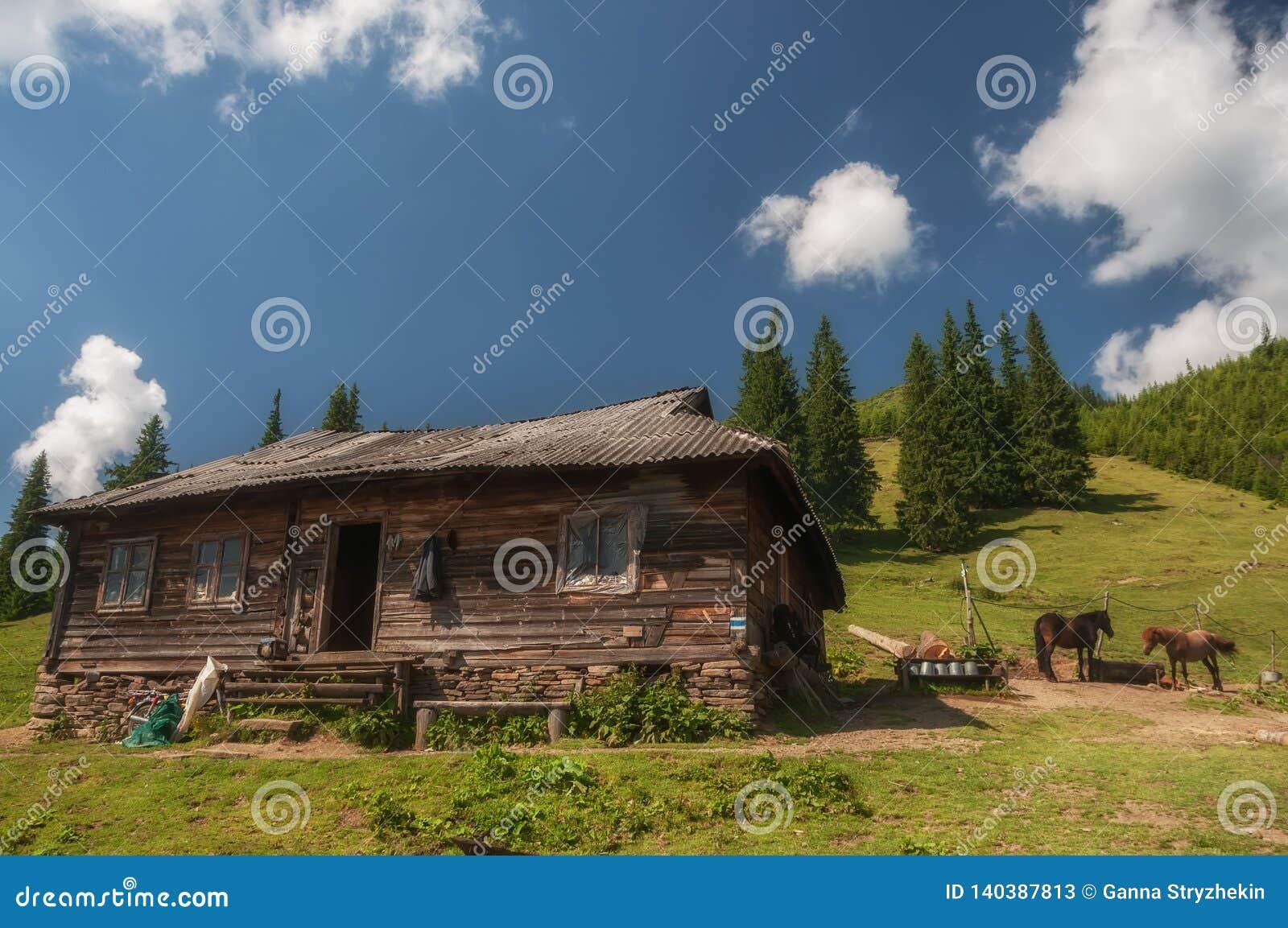 Traditionelle ukrainische hölzerne Hütte, in der Käse im Tal gemacht wird Kleine Kirche karpaten