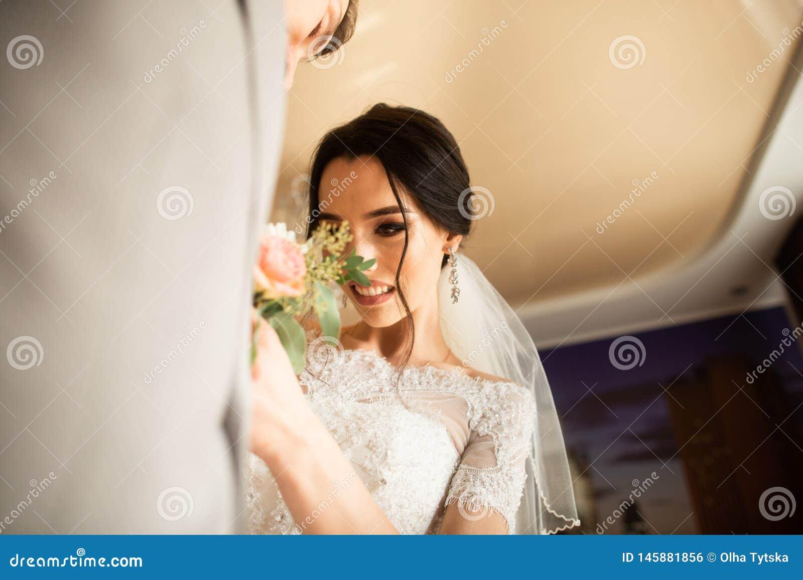 Traditionsgem?? ber?hrt die Braut im Haus einen kleinen Blumenstrau? f?r den Br?utigam Br?utigamblumenstrau? nahe bei der Hand au